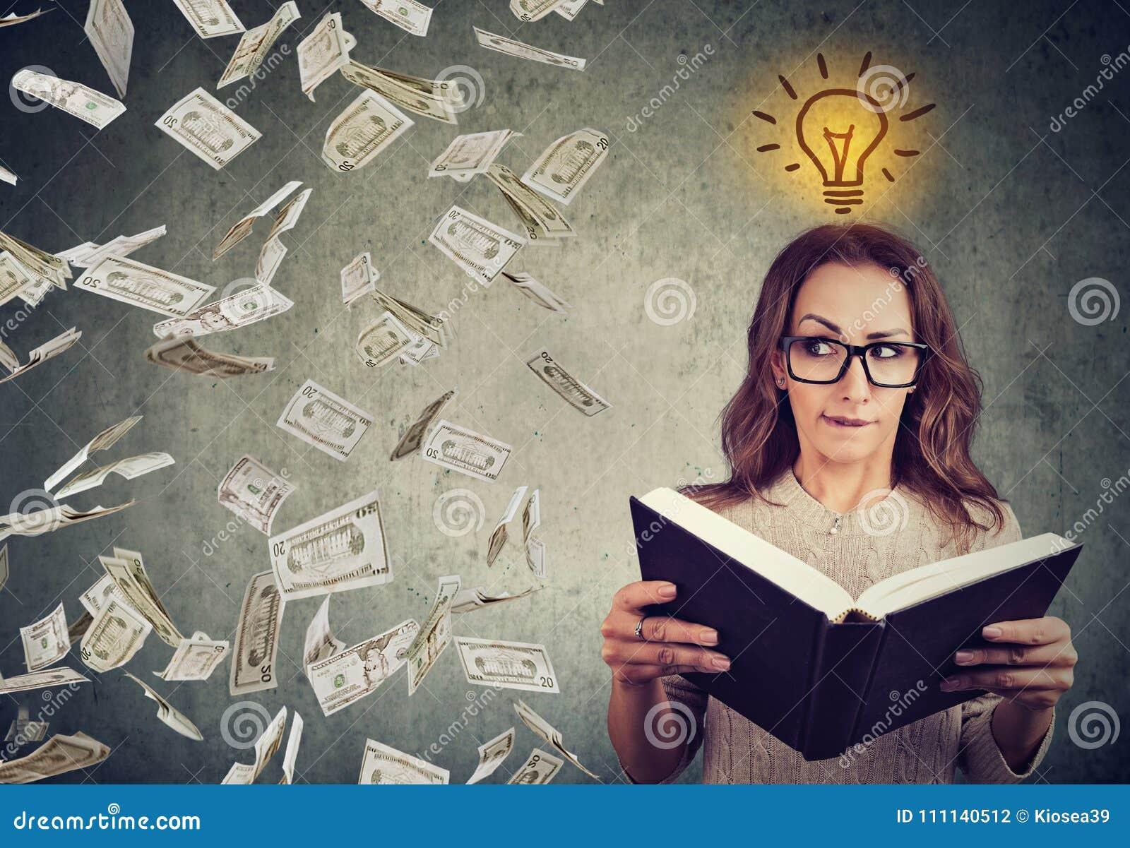 El estudiante que lee un libro tiene una idea brillante cómo ganar el dinero