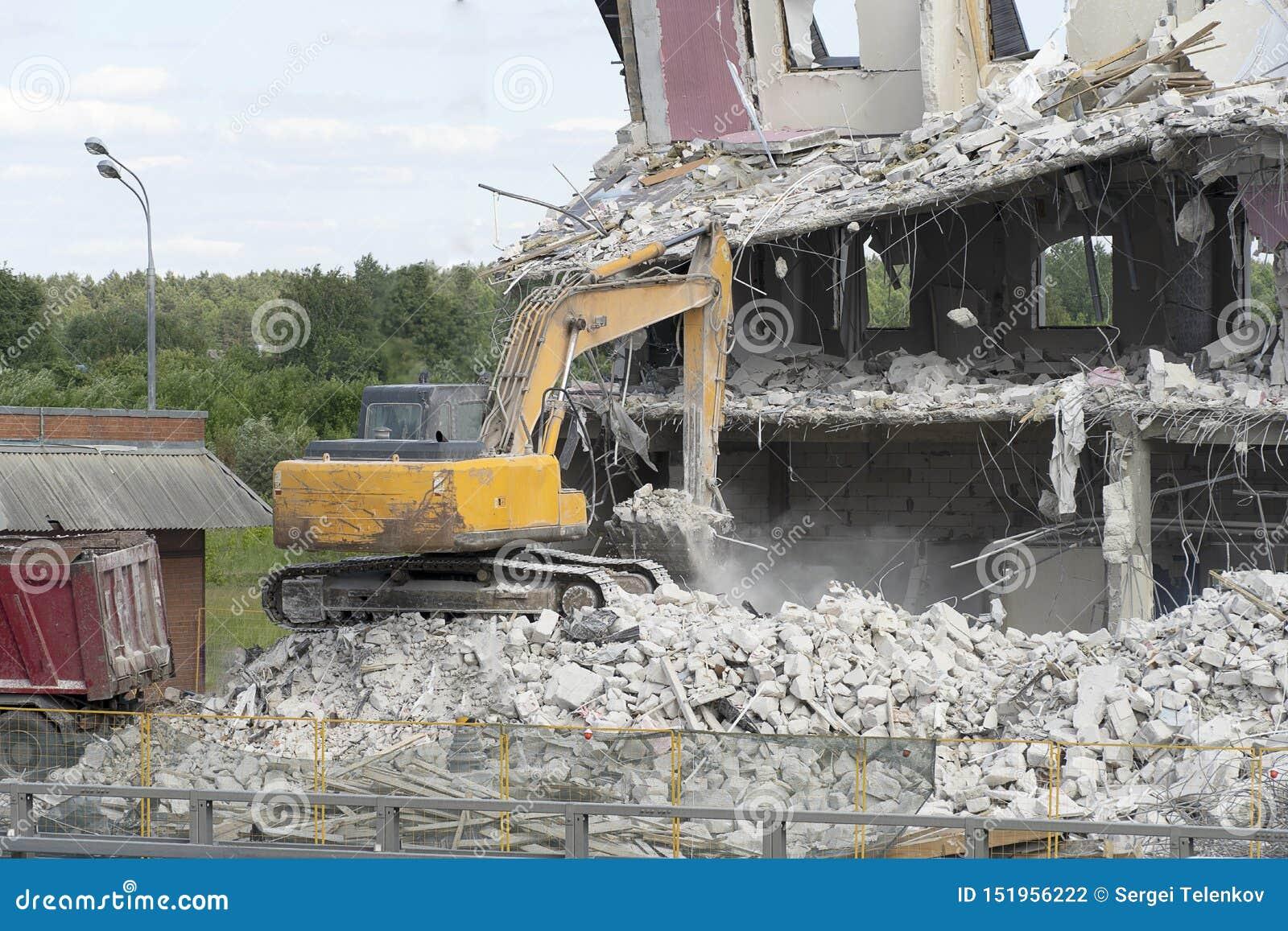 El excavador amarillo coge la basura de la construcción para cargar sobre un camión La técnica destruyó el edificio, es refuerzo,