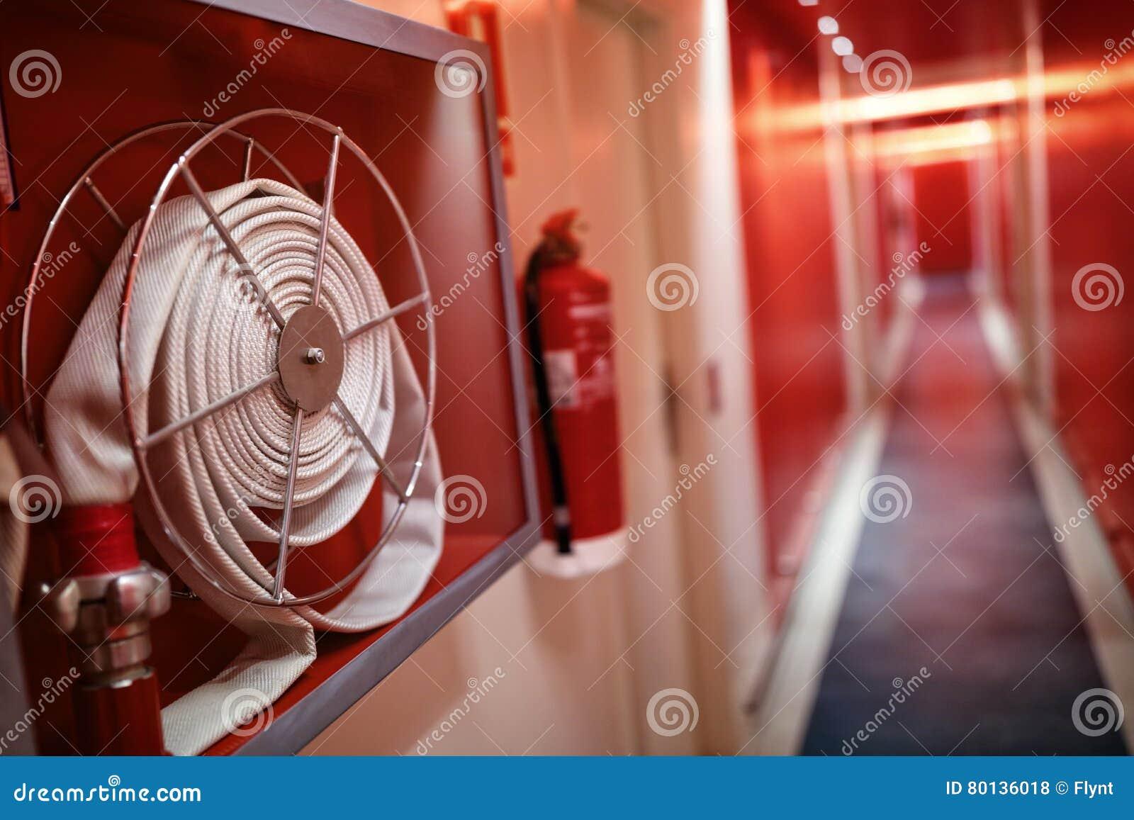 El extintor y la manguera aspan en pasillo del hotel