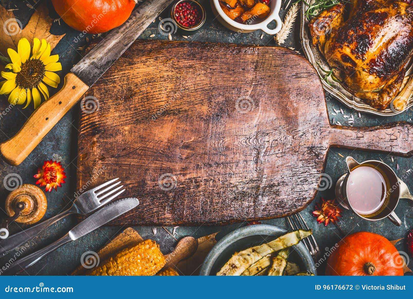 El fondo de la cena de la acción de gracias con el pavo, salsa, asó a la parrilla las verduras, maíz, cubiertos, calabaza, hojas
