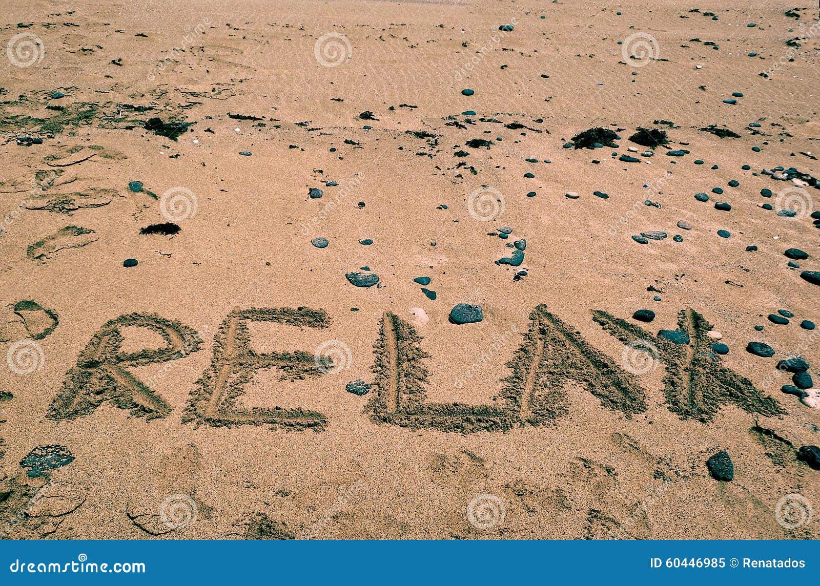 El fondo de los días de fiesta con RELAJA la palabra escrita en la playa arenosa Fondo de los días de fiesta Verano En relaje el