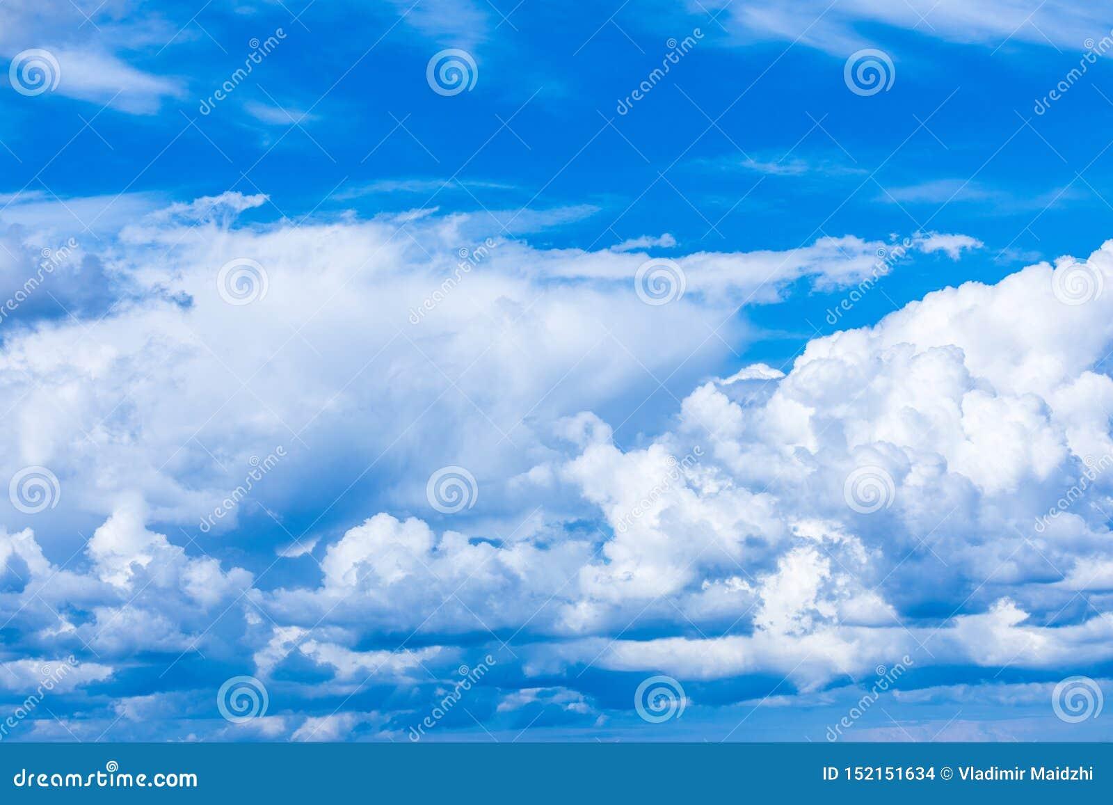 El fondo vivo del cielo o del cielo con las nubes blancas bajo rayos del sol