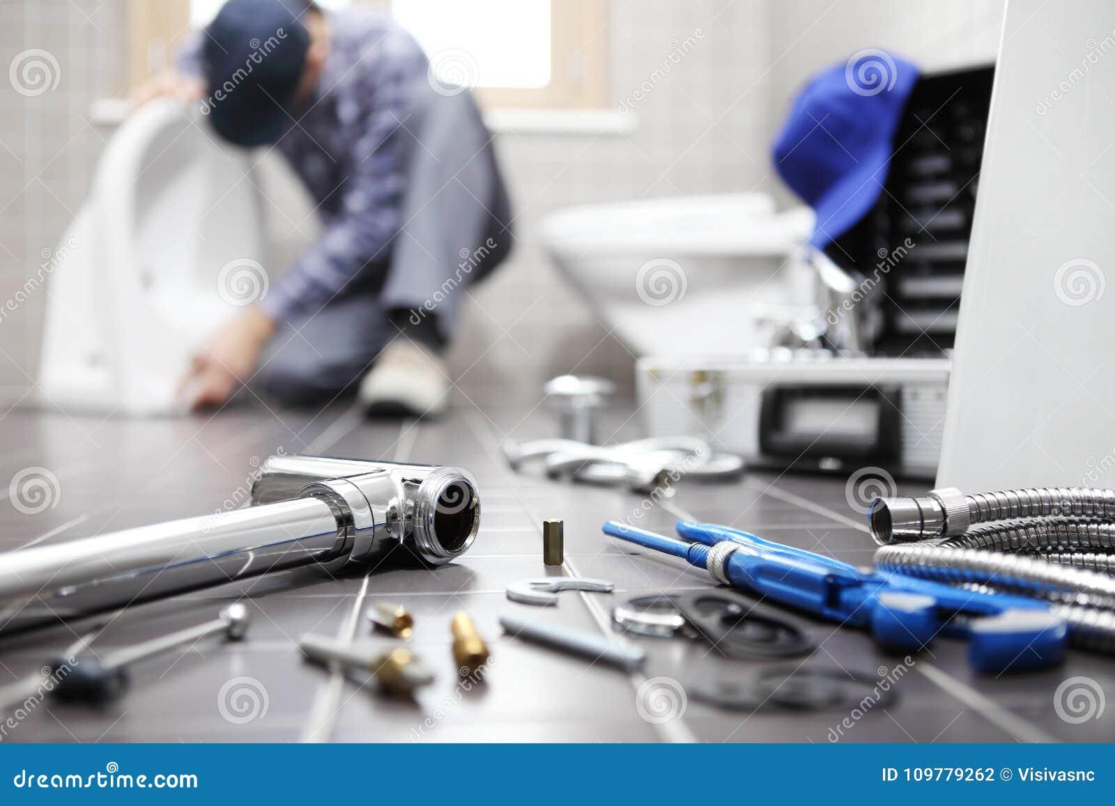 El fontanero en el trabajo en un cuarto de baño, sondeando servicio de reparación, monta