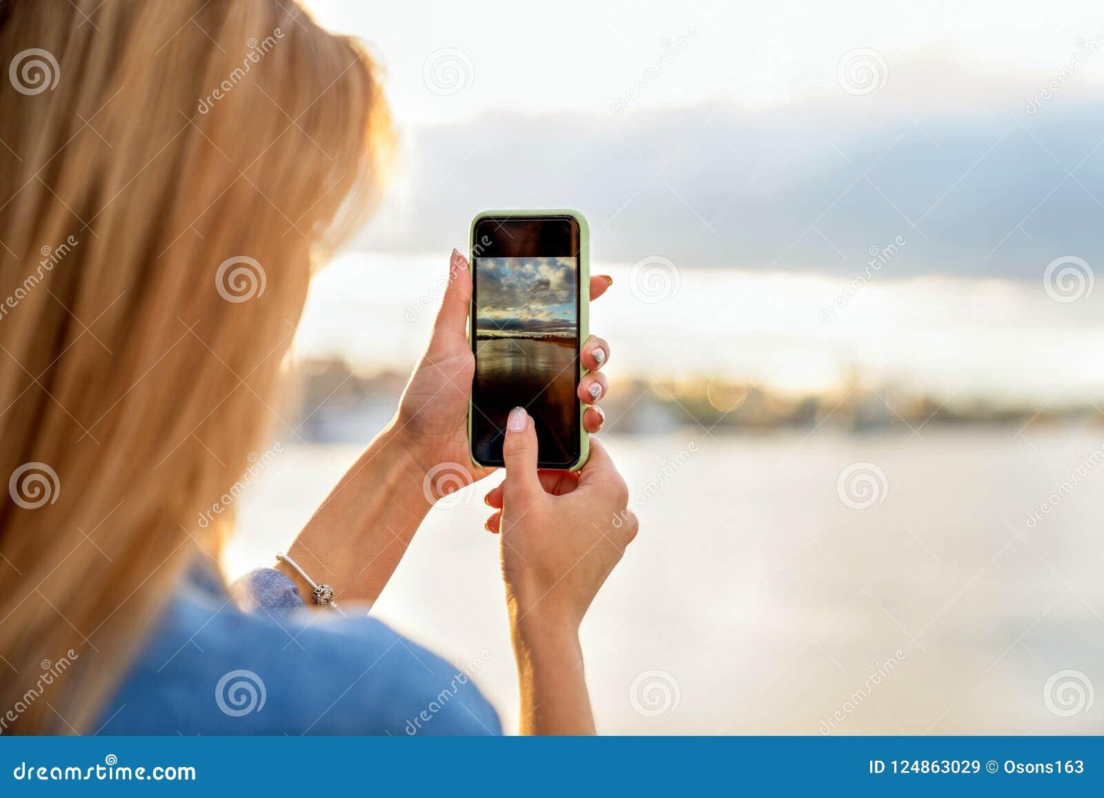 El freelancer de la muchacha en la puesta del sol habla en el teléfono y trabaja