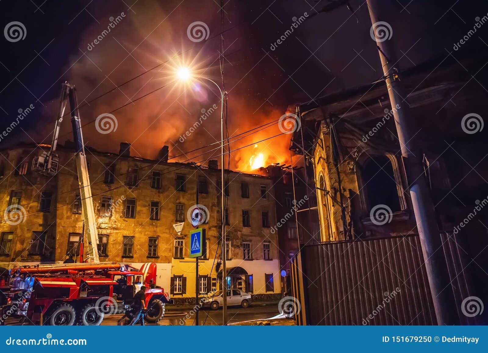 El fuego de la noche en la construcción de viviendas, bomberos lucha con la llama Concepto de la tragedia del desastre y del acci