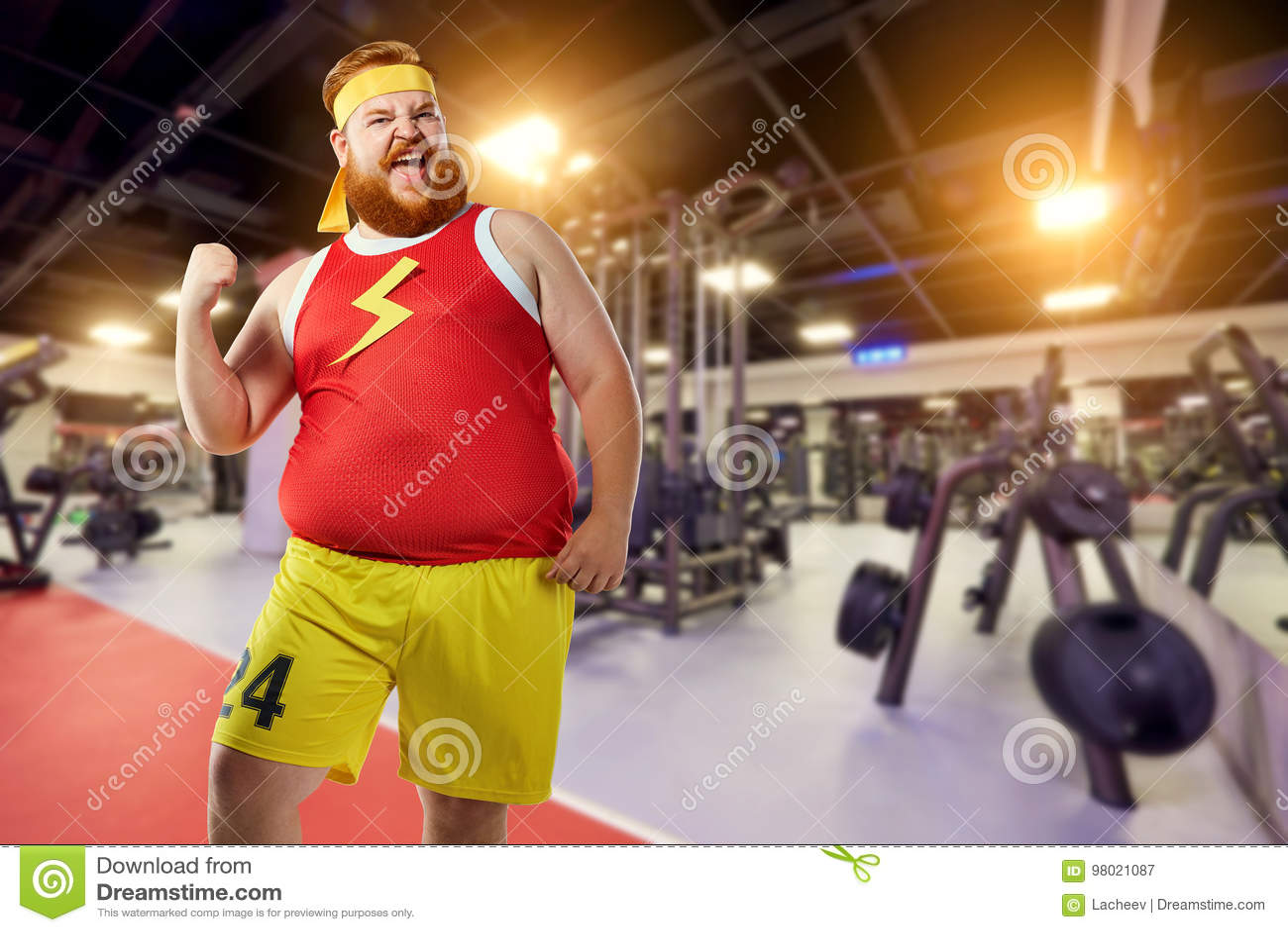 El ganador divertido gordo del hombre sonríe en ropa de los deportes en el gimnasio