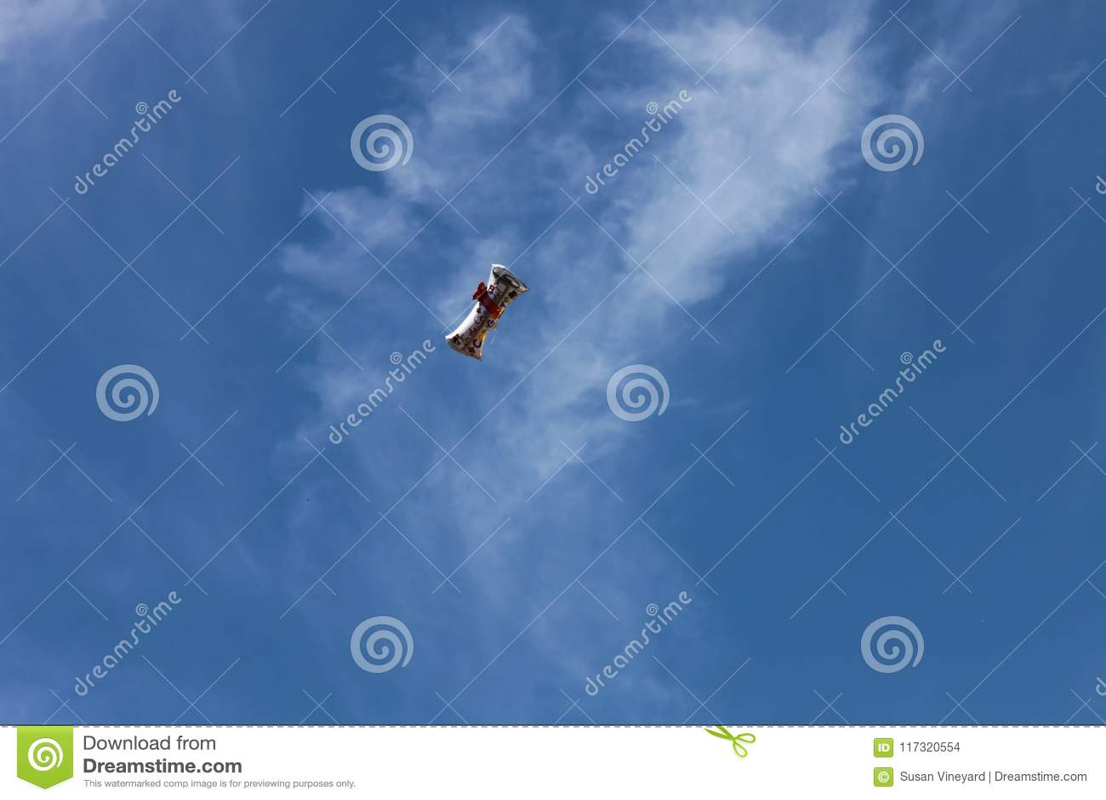 El globo formó como un diploma que dice para el graduado que flota en un cielo azul con las nubes whispy arriba sobre un ceremon