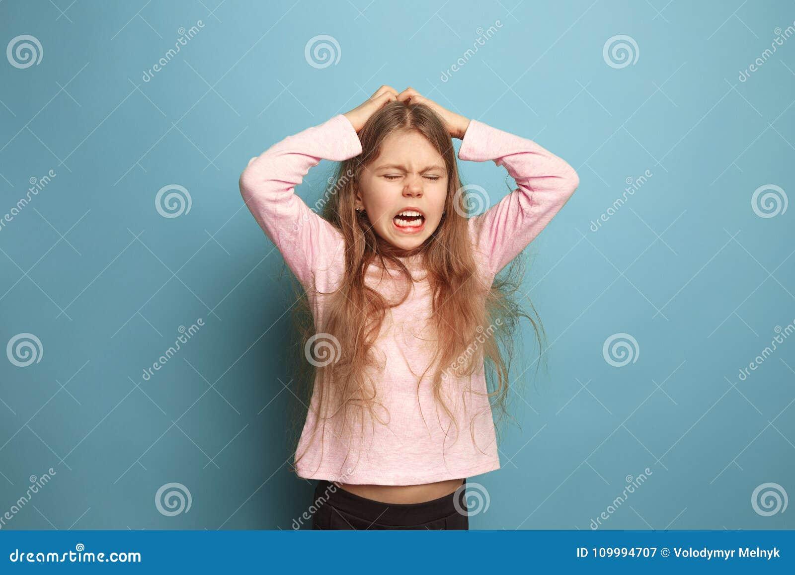 El grito Muchacha adolescente en un fondo azul Expresiones faciales y concepto de las emociones de la gente