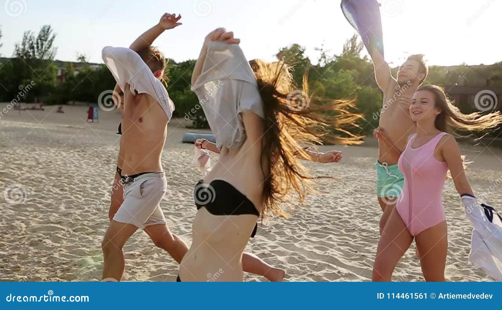 El Grupo De Amigos Desnuda El Funcionamiento En La Agua De Mar En Puesta Del Sol Y Lanza Las Camisas En La Playa Gente Feliz Aleg