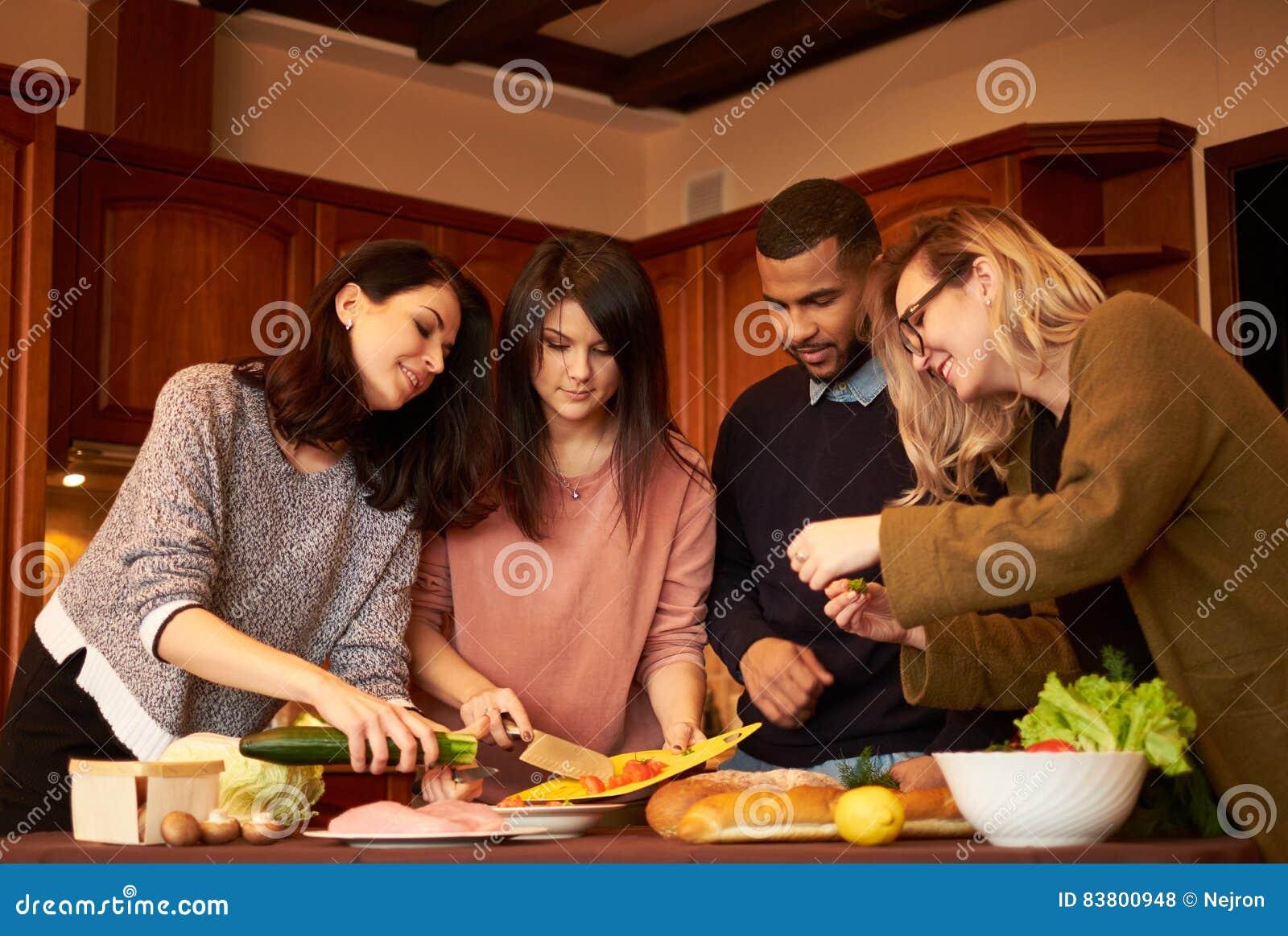 El grupo de amigos jovenes étnicos multi en cocina se prepara para el partido