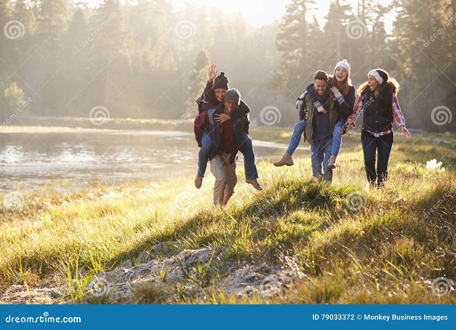 El grupo de amigos se divierte que llevan a cuestas por un lago