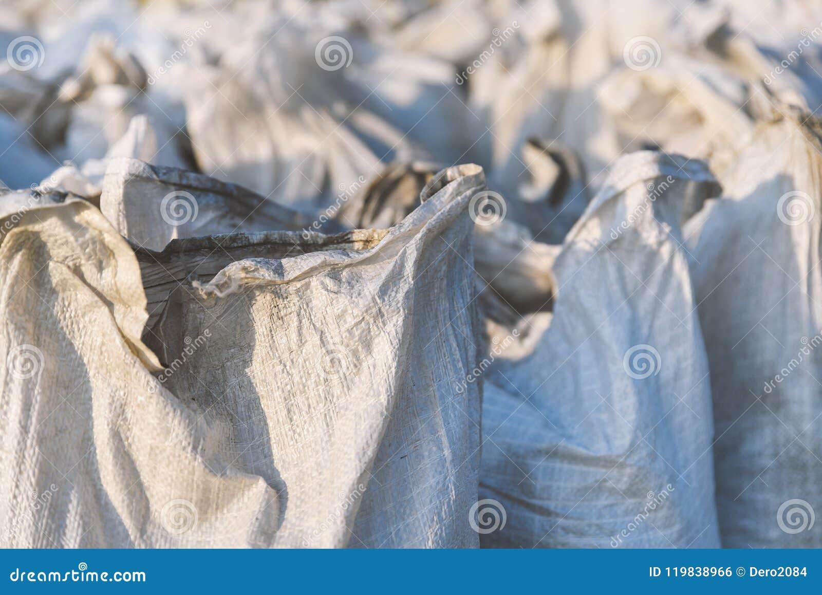 El grupo de bolsos llenados del polipropileno, el embalar de las mercancías para el transporte y el almacenamiento en almacén, pl