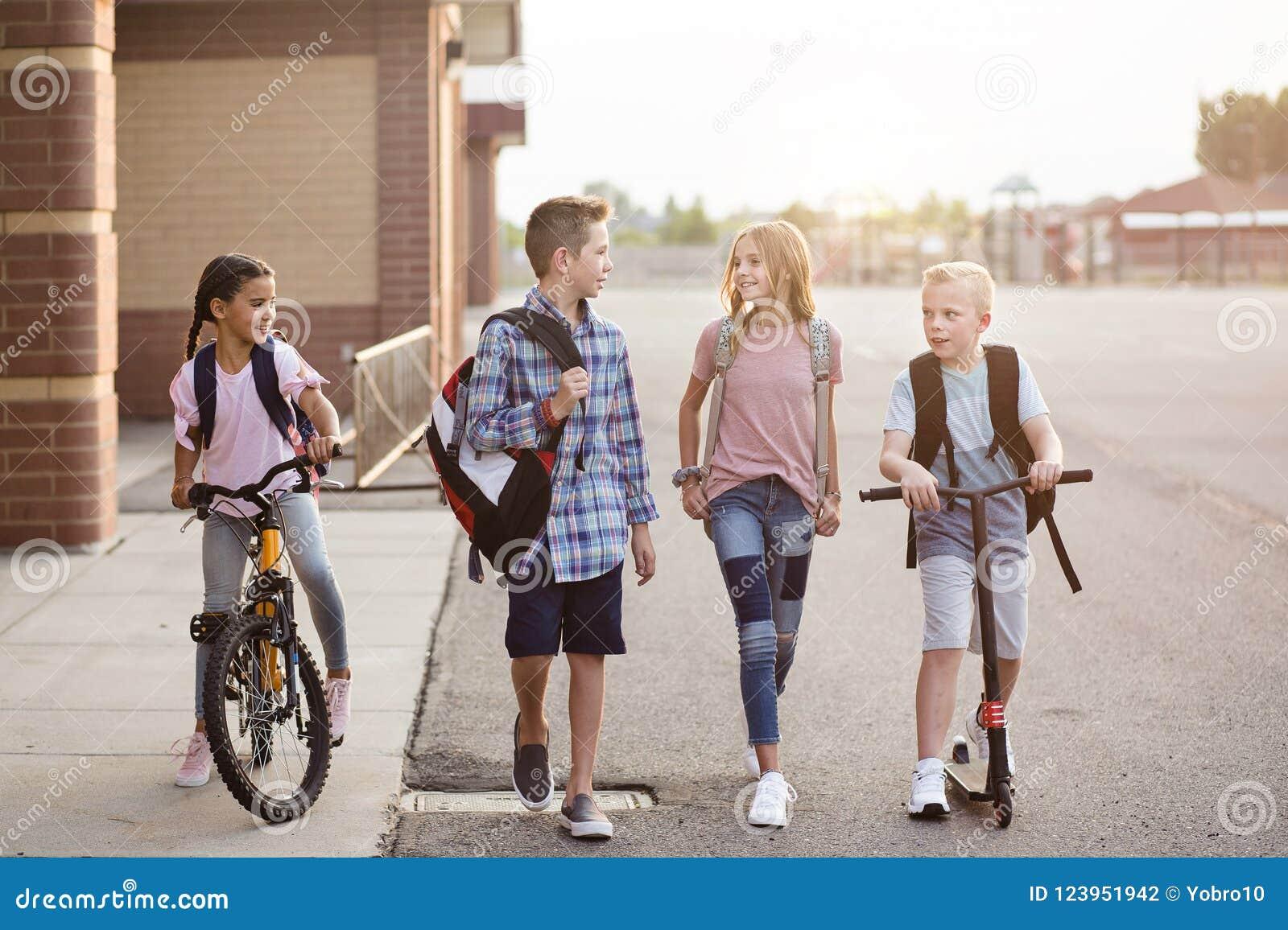 El grupo de escuela embroma hablar y caminar a casa de escuela junto