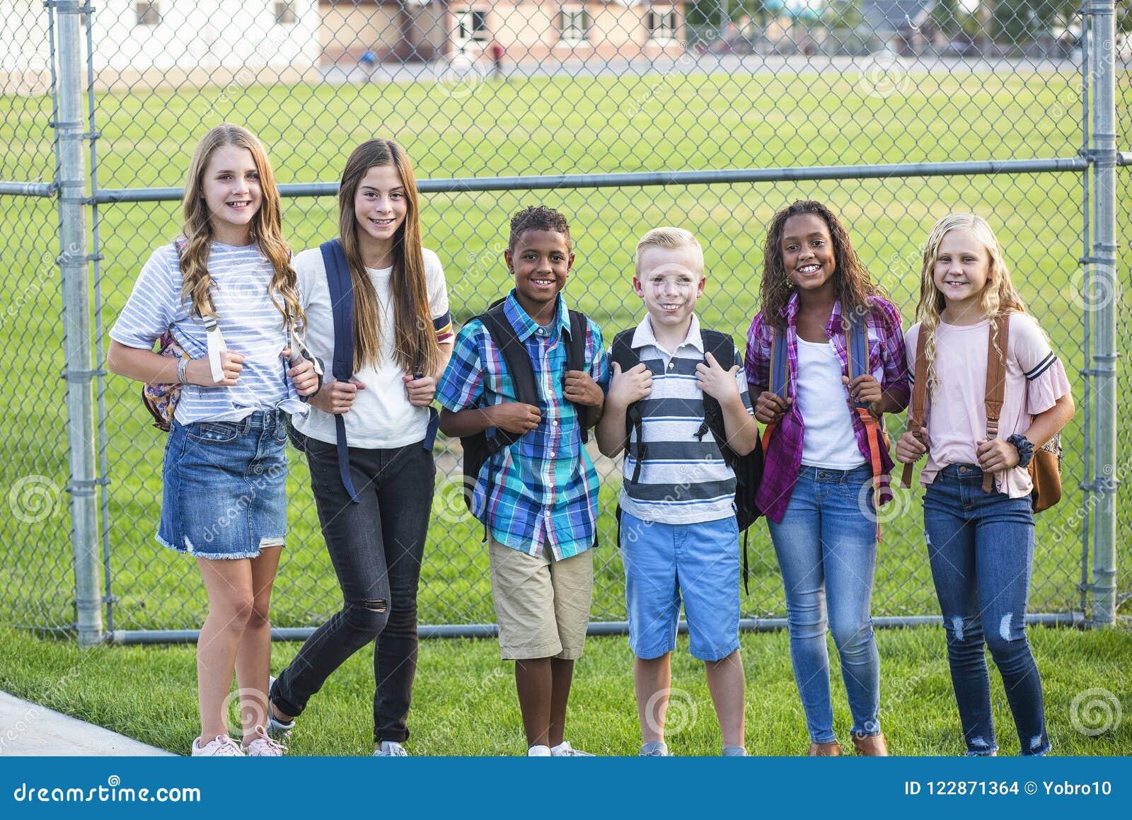 El grupo de escuela embroma la sonrisa mientras que se coloca en un patio de la escuela primaria