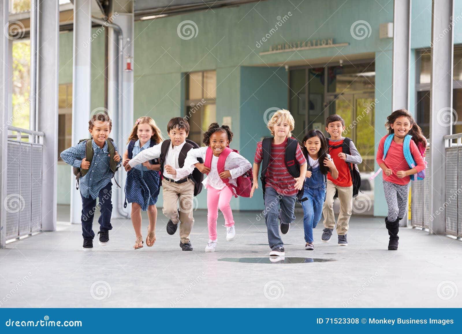 El grupo de escuela primaria embroma el funcionamiento en un pasillo de la escuela