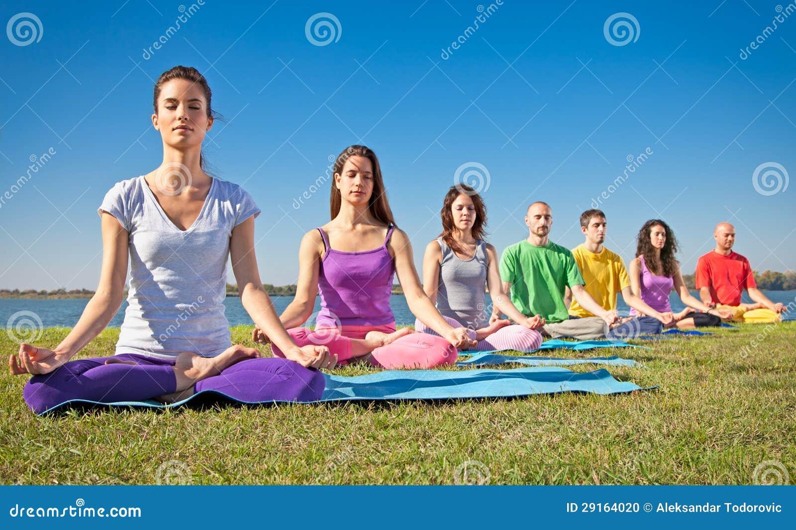 El grupo de gente joven tiene meditación en clase de la yoga.