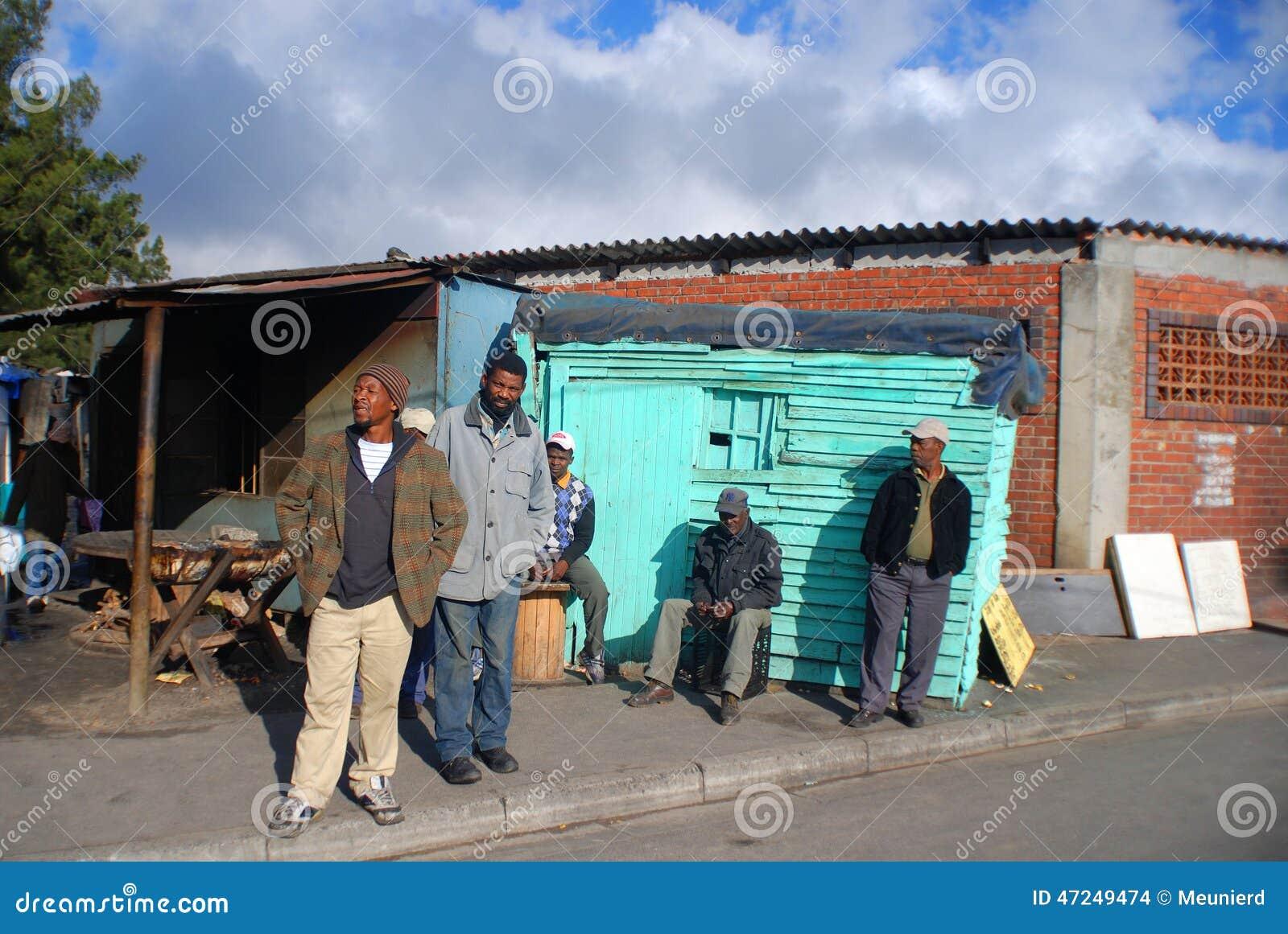 El grupo de hombres camina en la calle en el municipio de Khayelitsha