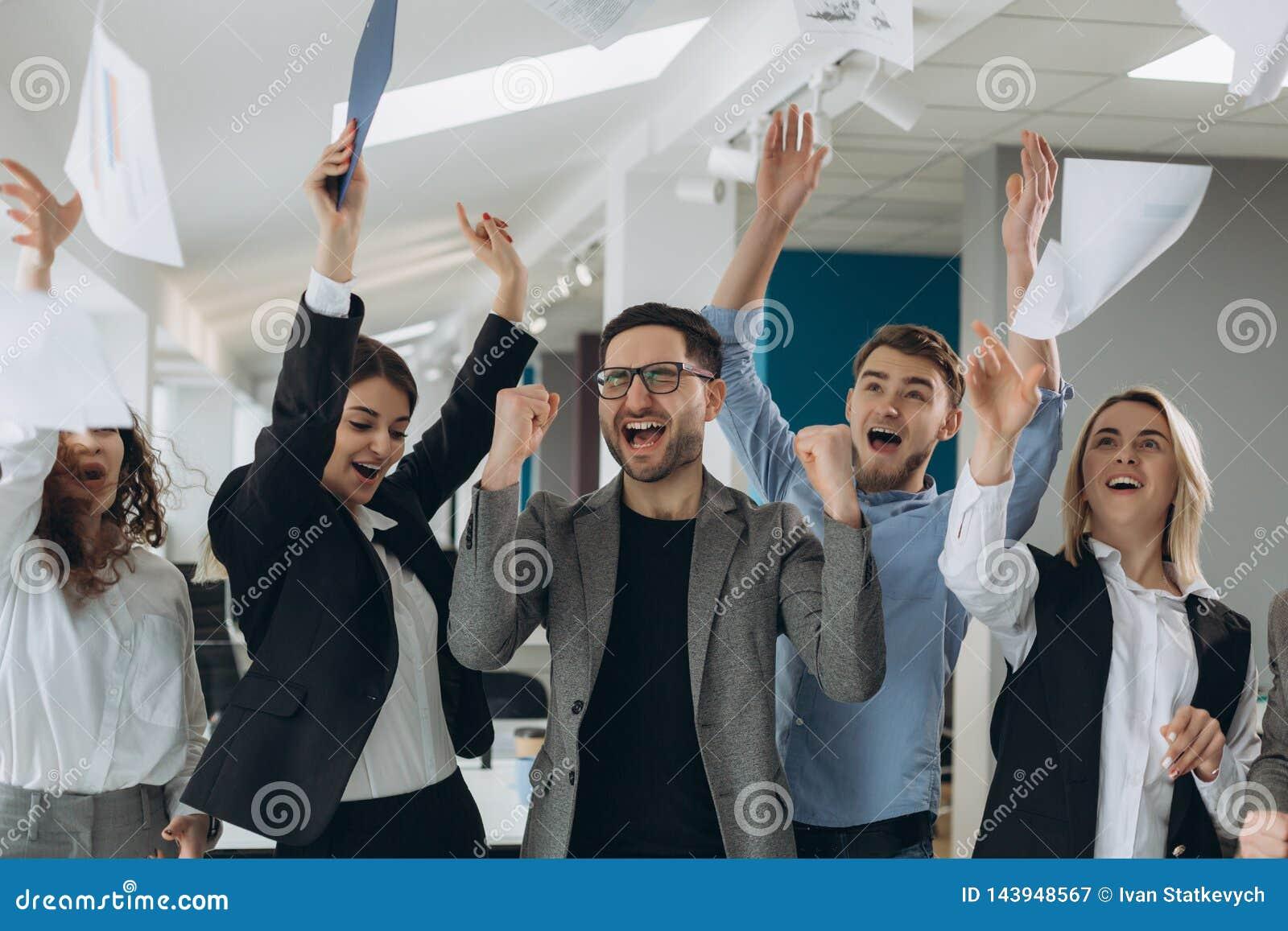 El grupo de hombres de negocios que celebran lanzando sus documentos comerciales y los documentos vuelan en el aire, poder de la
