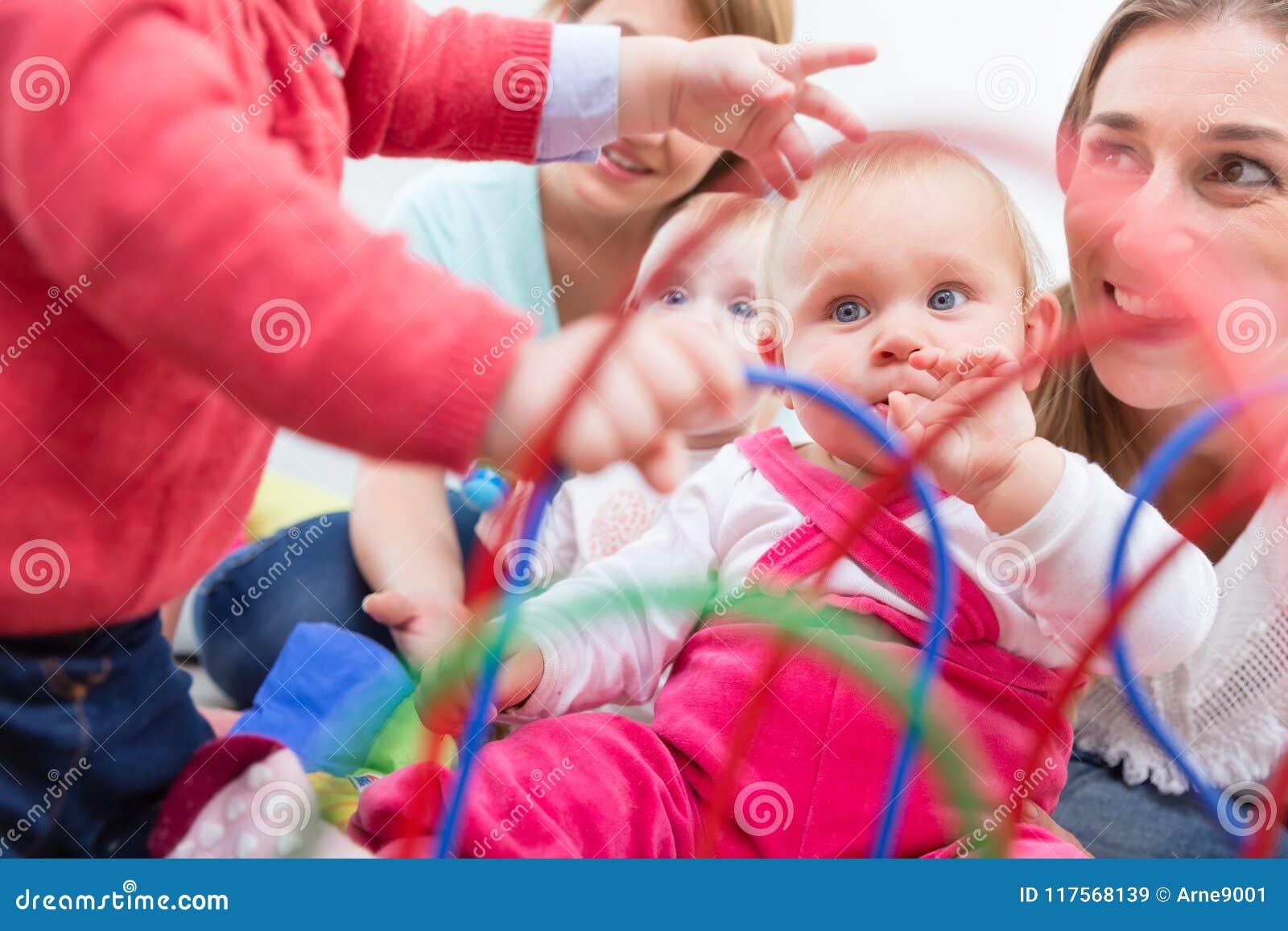 El grupo de madres jovenes felices que miran a sus bebés lindos y sanos juega