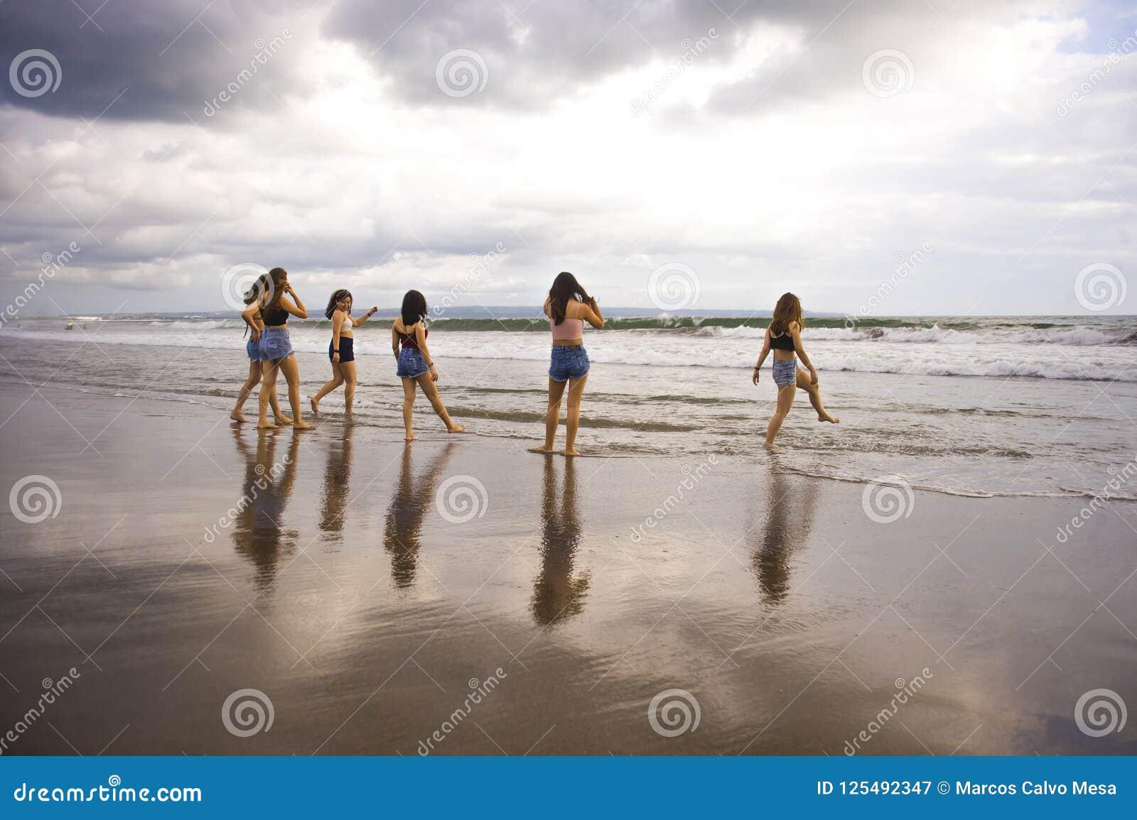El grupo de mujeres jovenes felices y emocionadas que gozan divirtiéndose en la playa hermosa de la puesta del sol en vacaciones