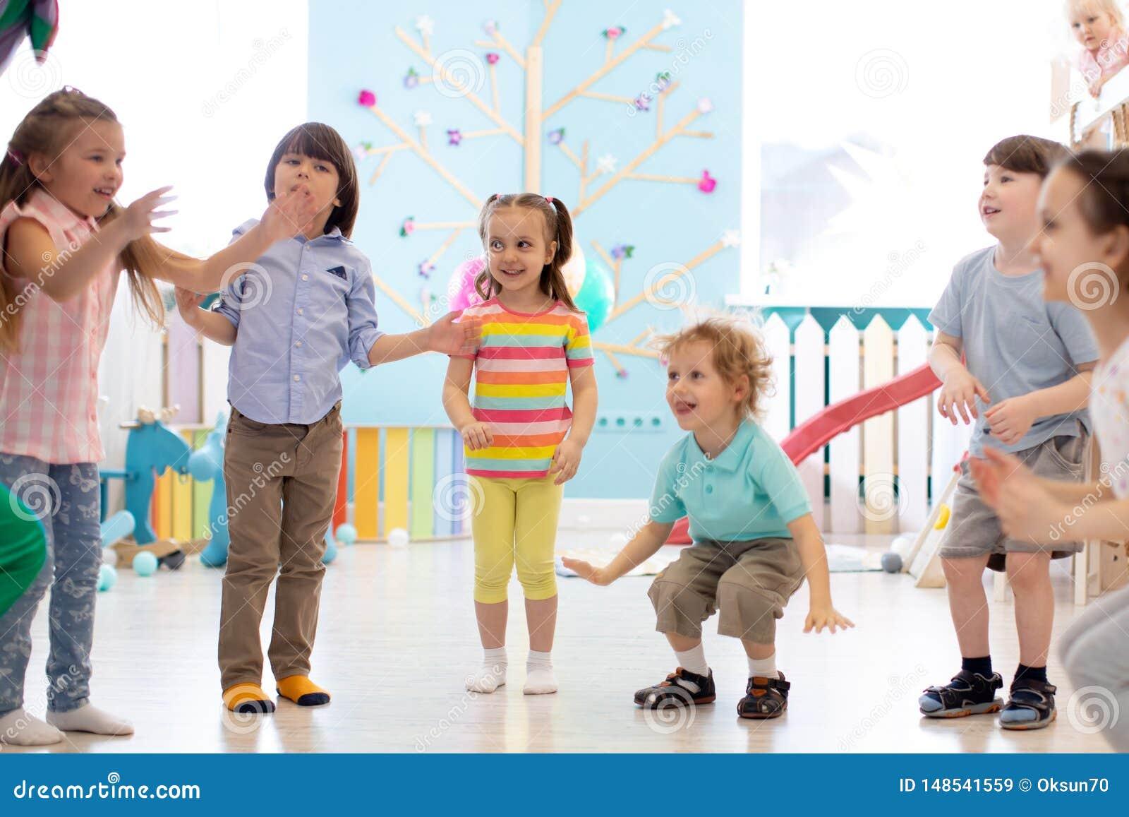 El grupo de niños felices salta interior Los ni?os juegan juntos