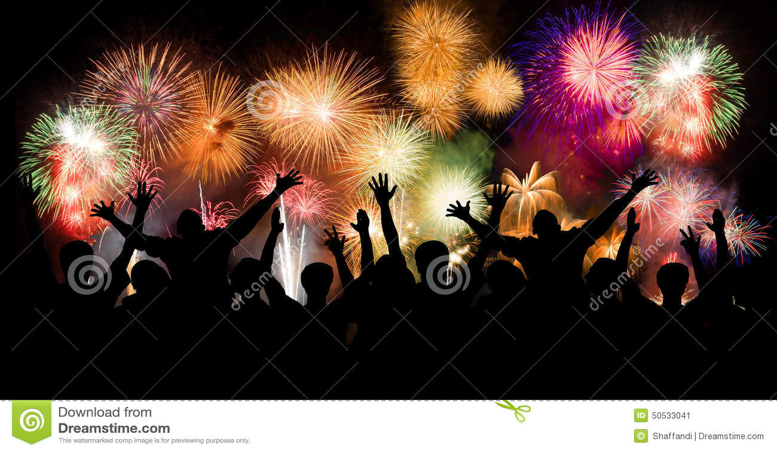 El grupo de personas que goza de los fuegos artificiales espectaculares muestra en un carnaval o un día de fiesta