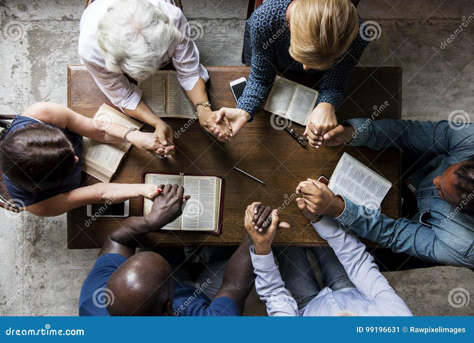 El grupo de personas que lleva a cabo las manos que ruegan la adoración cree