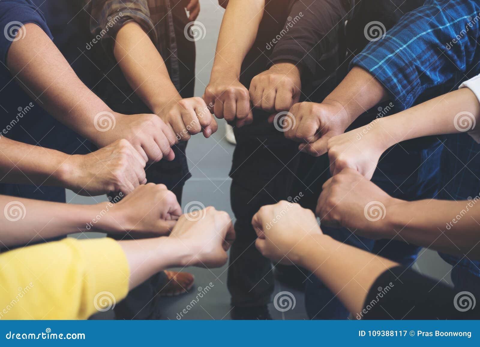 El grupo de trabajo del equipo del negocio se unen a sus manos así como poder y acertados