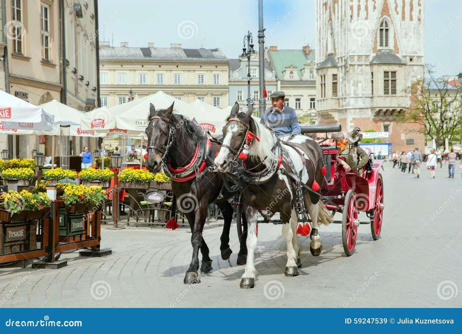 El grupo de turistas tiene excurtion en el carro de los caballos en la parte histórica de Kraków