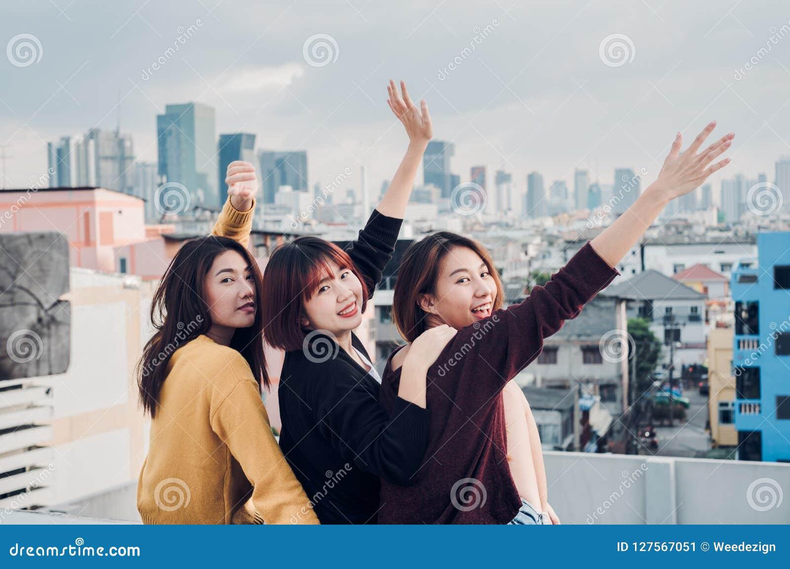 El grupo feliz de amigas de Asia goza y el brazo para arriba relaja actitud en