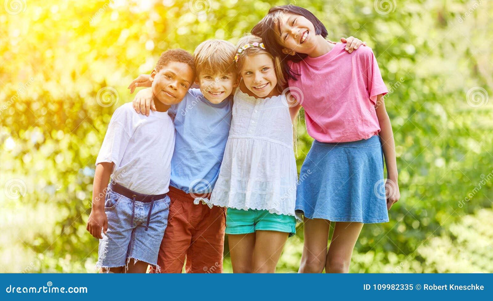 El grupo multicultural de niños se abraza en verano