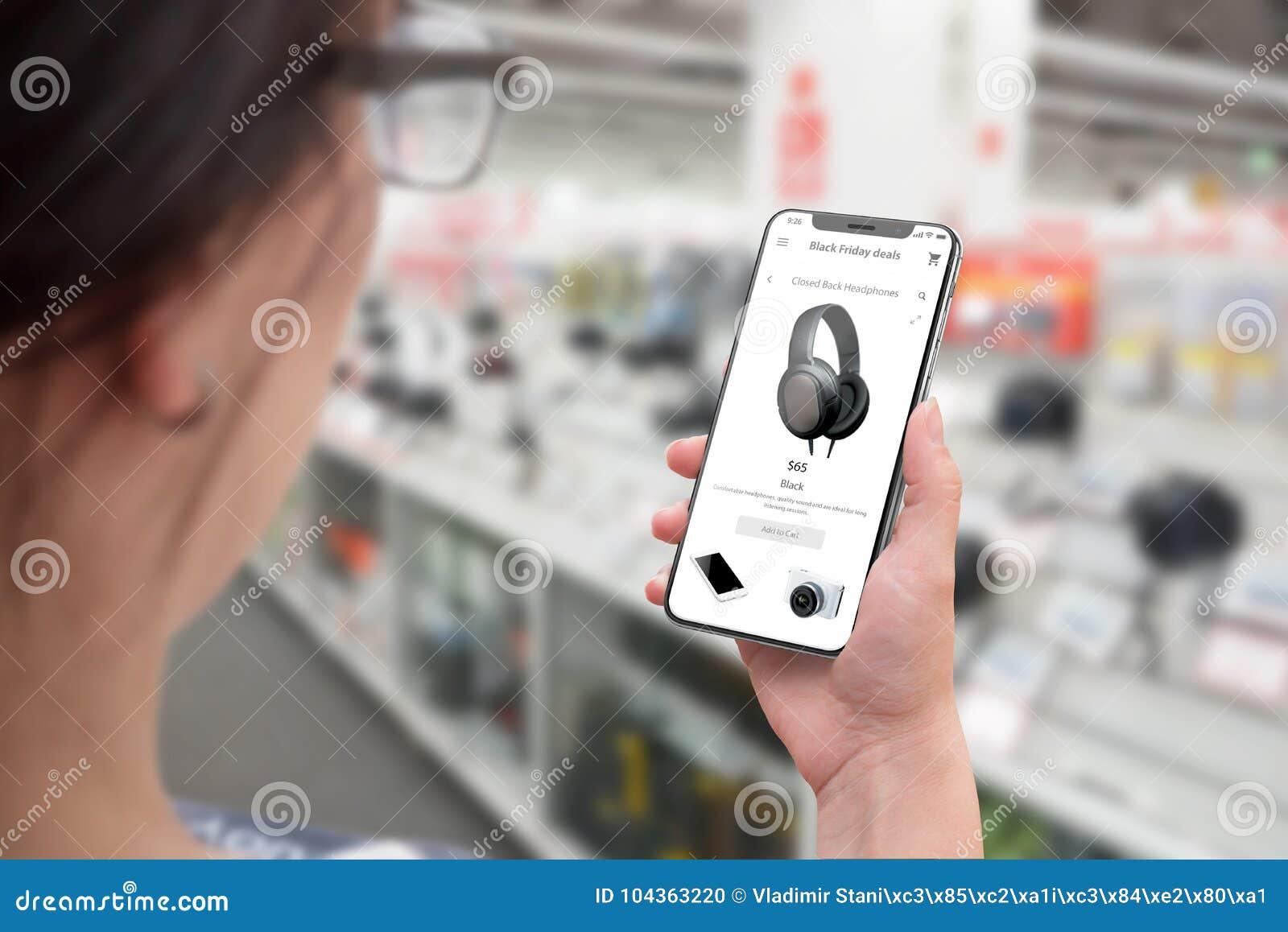El hacer compras con smartphone Mujer que usa el sitio web y la búsqueda de la tienda en línea para los descuentos de la tecnolog