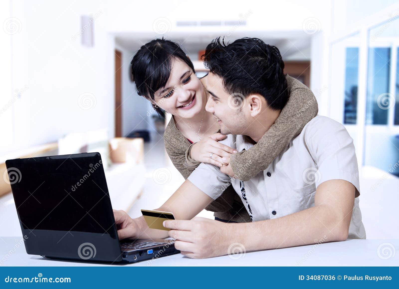 El hacer compras en línea de los pares asiáticos jovenes en casa