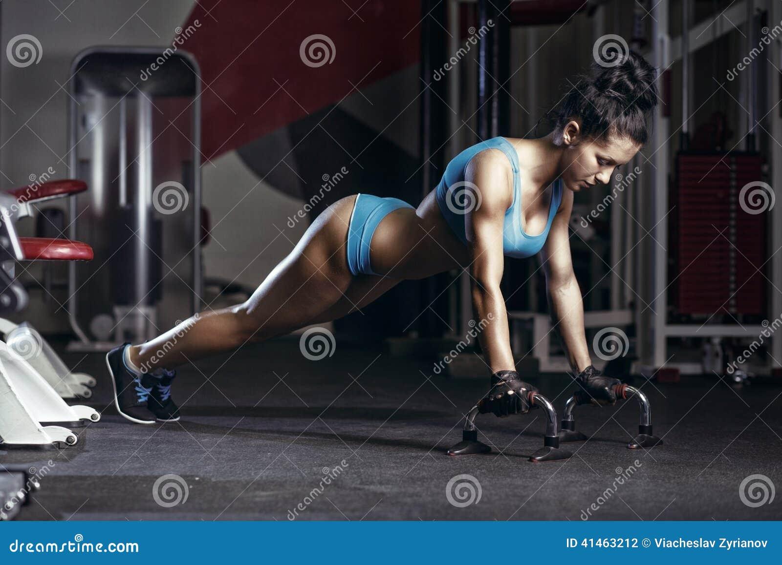 El hacer de la mujer de la aptitud empuja para arriba hacia adentro el gimnasio