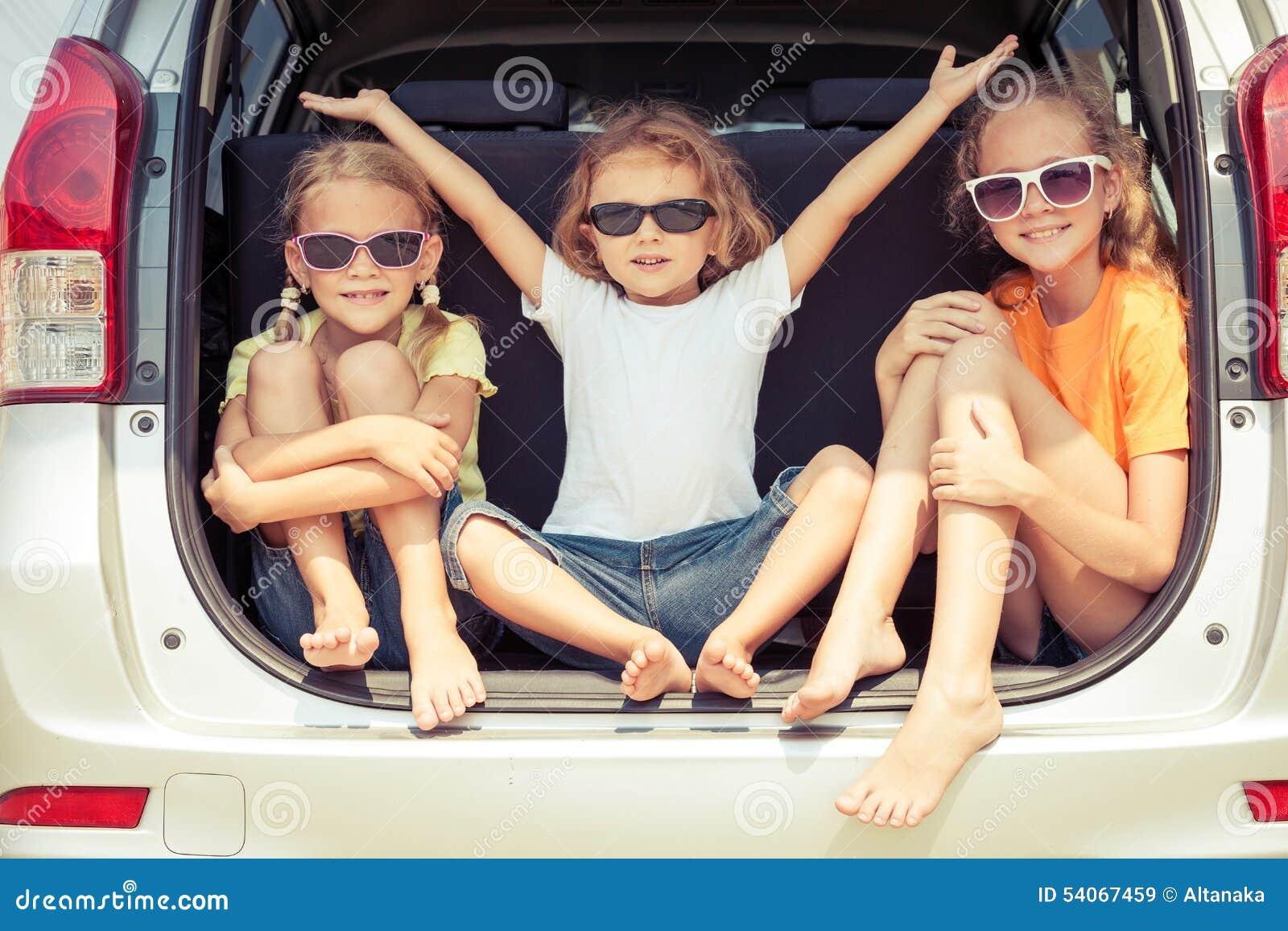El hermano feliz y sus dos hermanas se están sentando en el coche