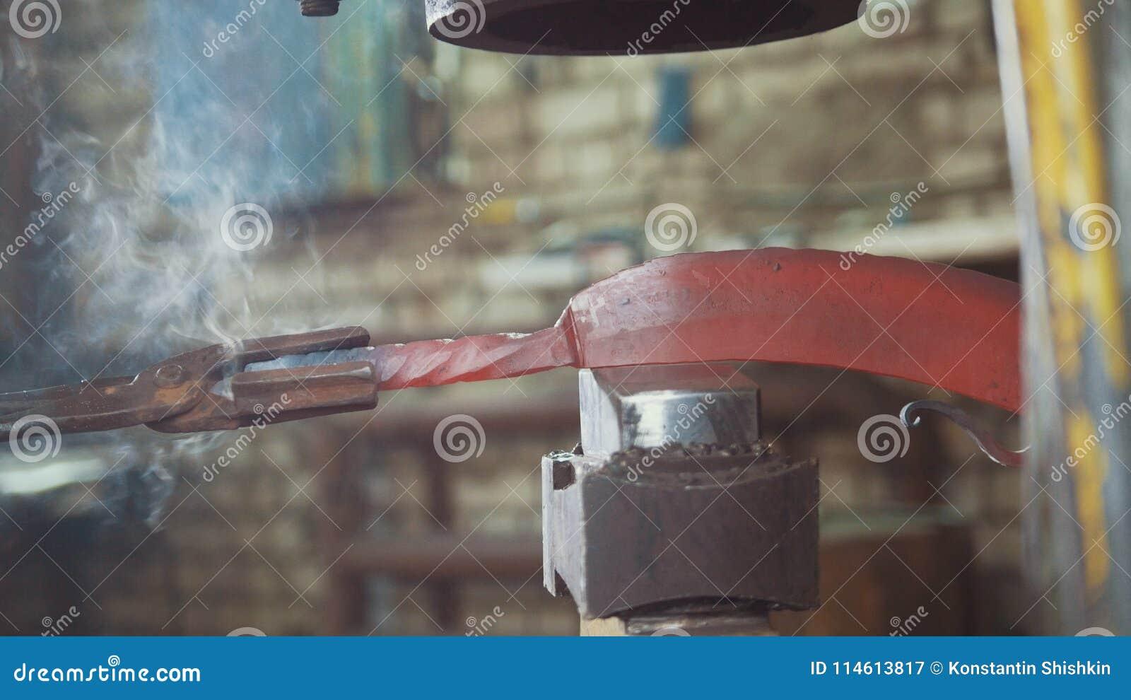 El herrero que forja manualmente en la herrería