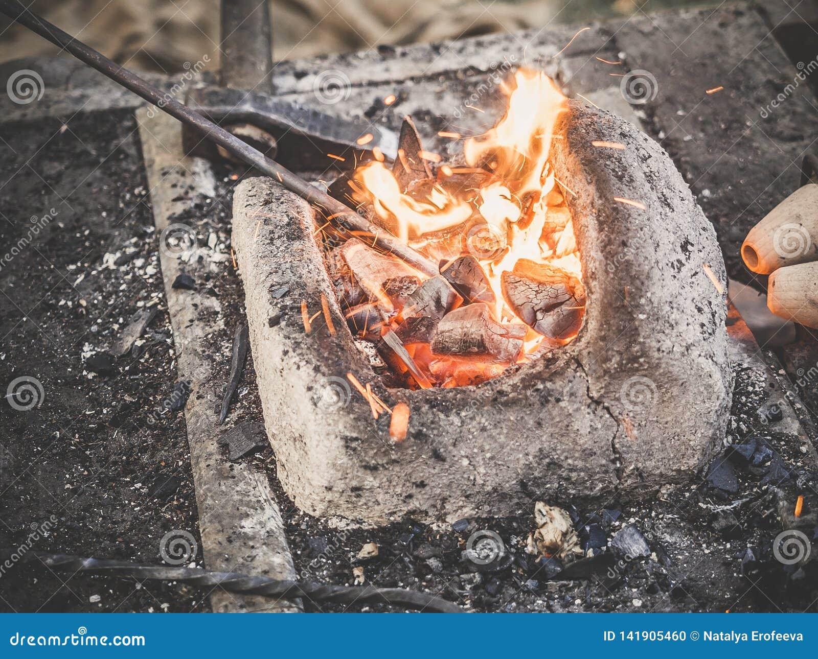 El herrero sostiene el billete sobre los carbones calientes en un horno de la arcilla fabricación de calefacción de la espada del