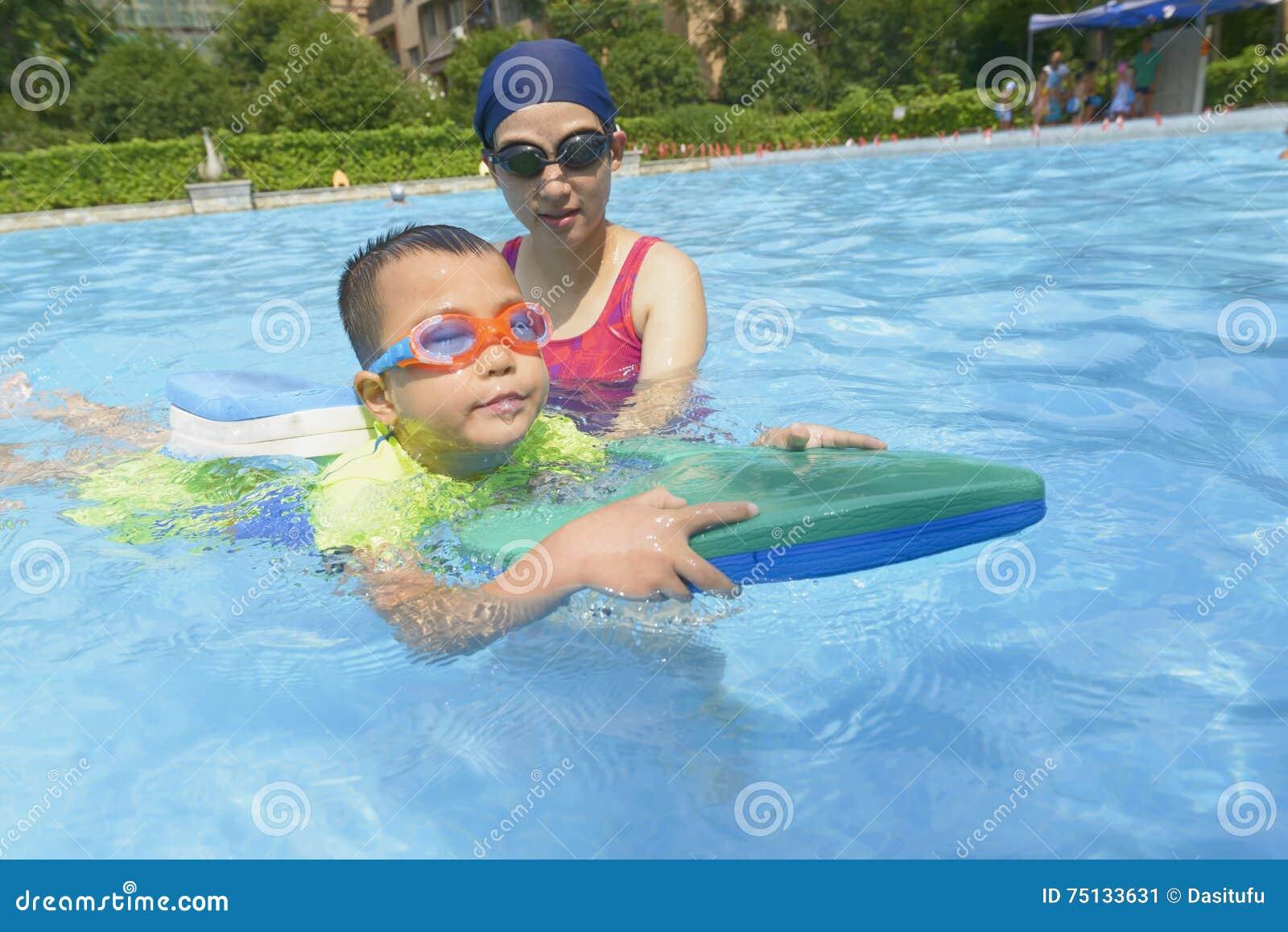 El hijo de enseñanza de la mamá aprende nadar en verano