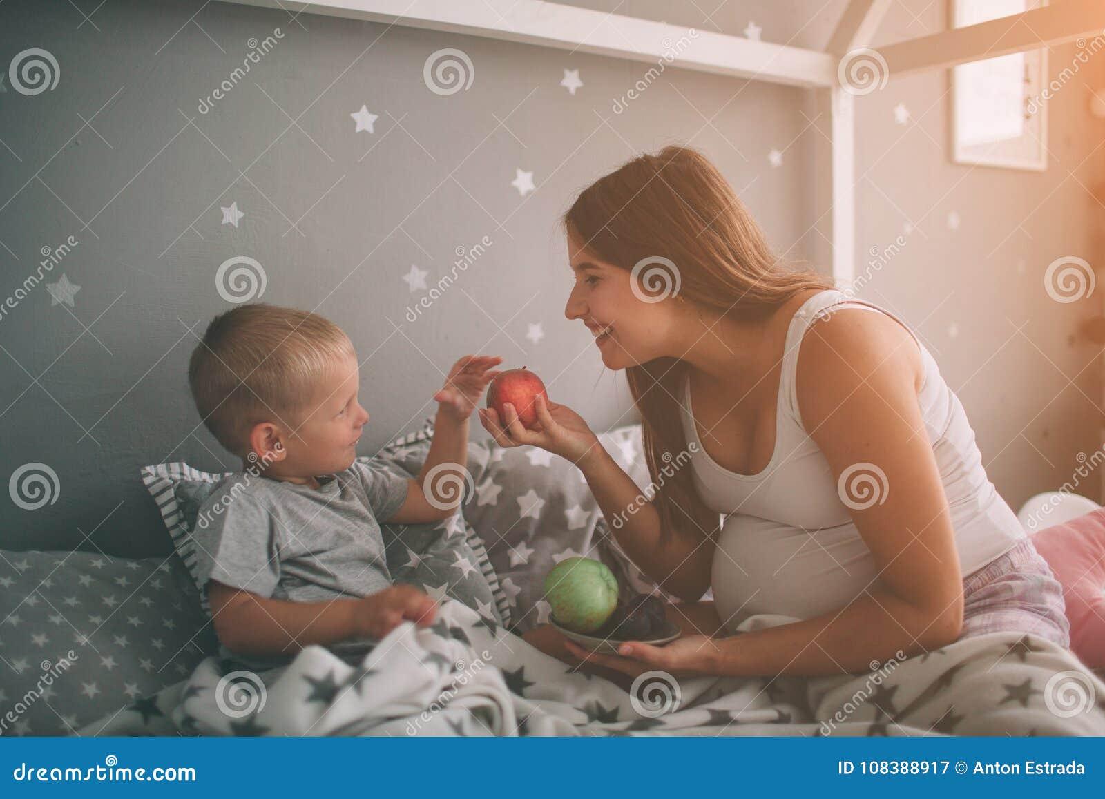 El hijo embarazada de la madre y del niño pequeño está comiendo una manzana y un melocotón en el hogar de la cama t por la mañana