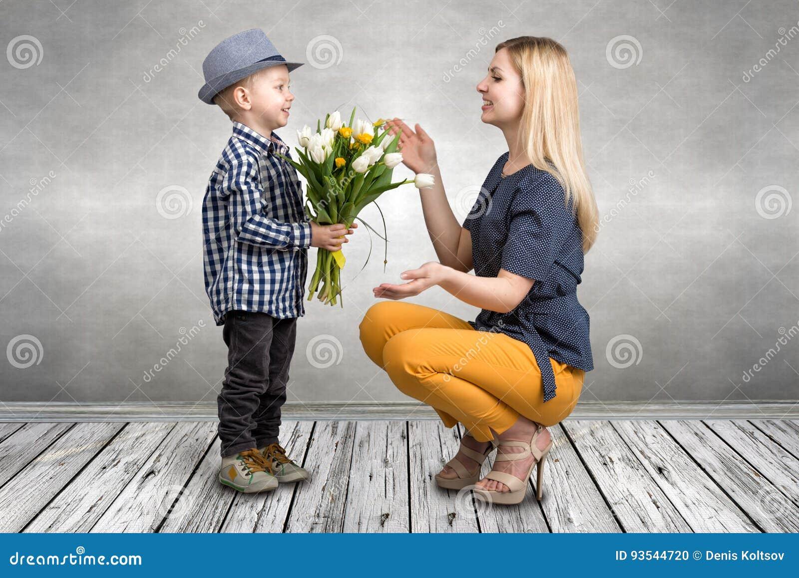 El hijo joven da a su madre querida un ramo de tulipanes hermosos Primavera, concepto de vacaciones de familia Día del `s de las