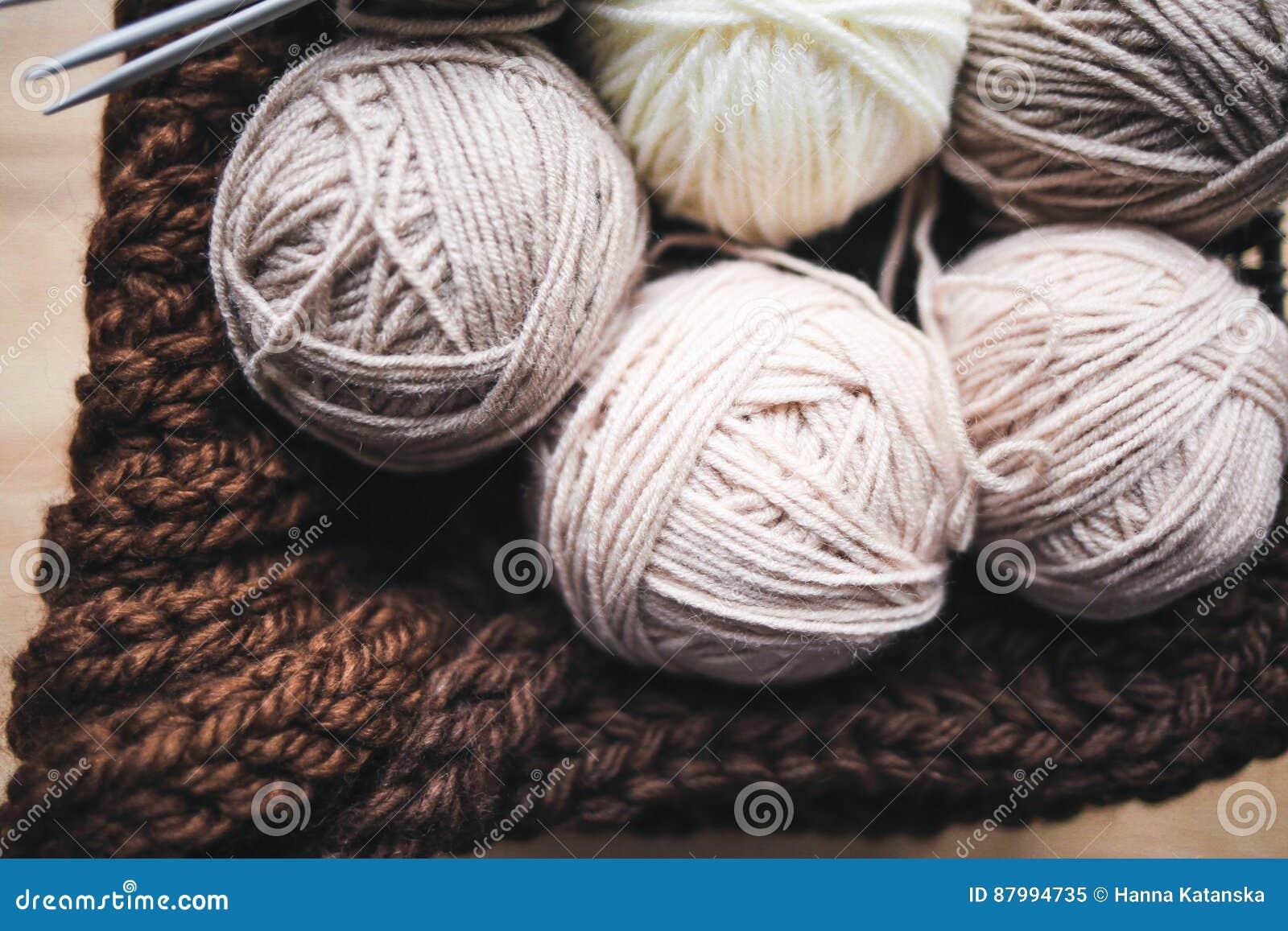 El hilado beige, las agujas que hacen punto y una bufanda marrón están en la cesta