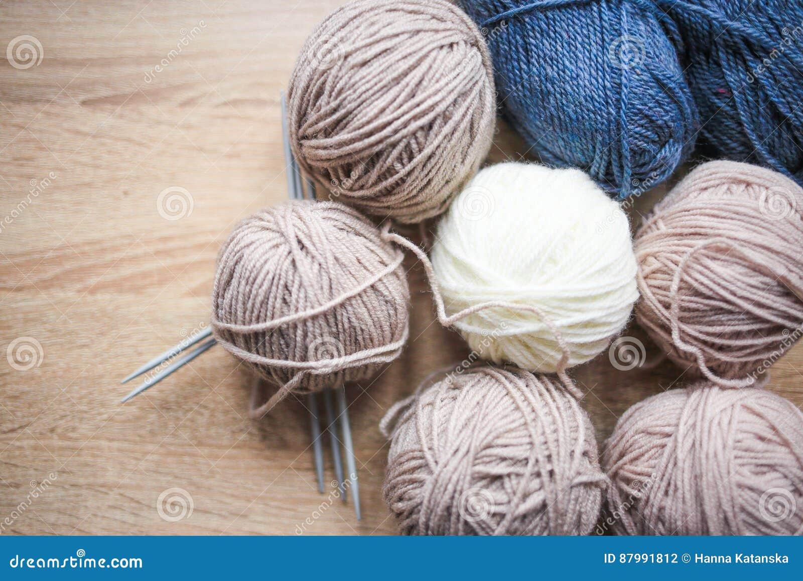 El hilado de las agujas que hacen punto, del beige, blanco y azul está en la tabla
