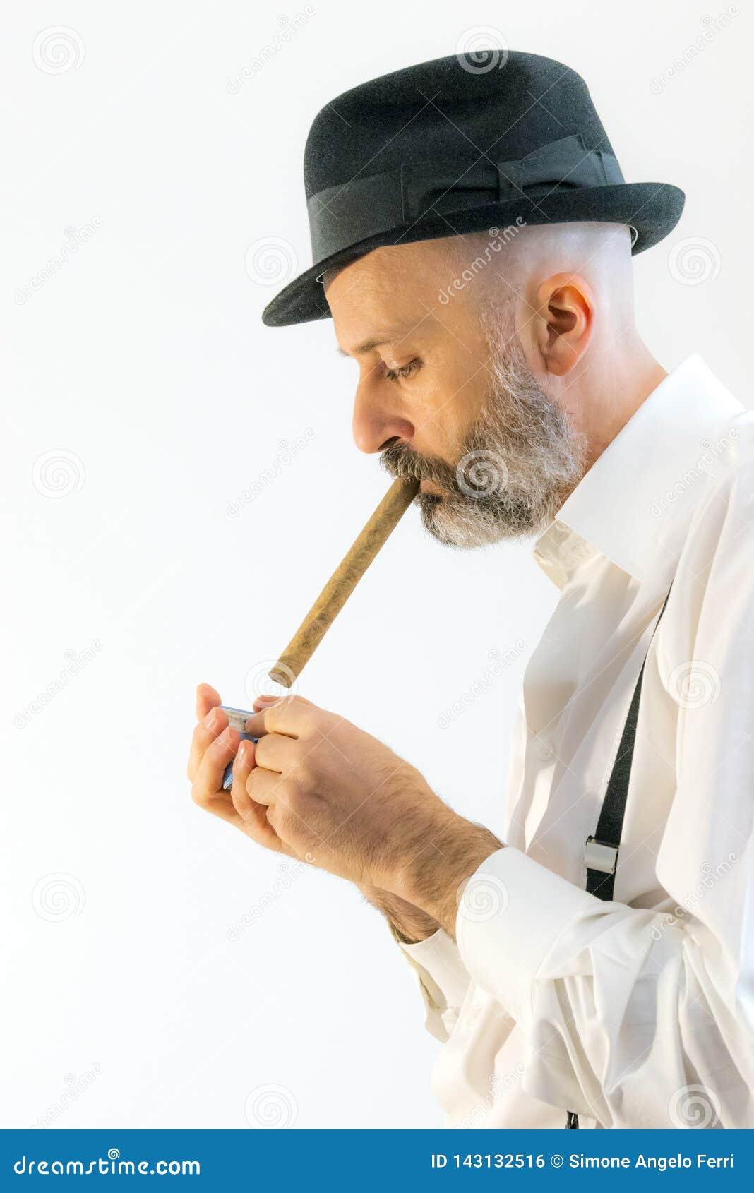 El hombre adulto está fumando el cigarro con el sombrero