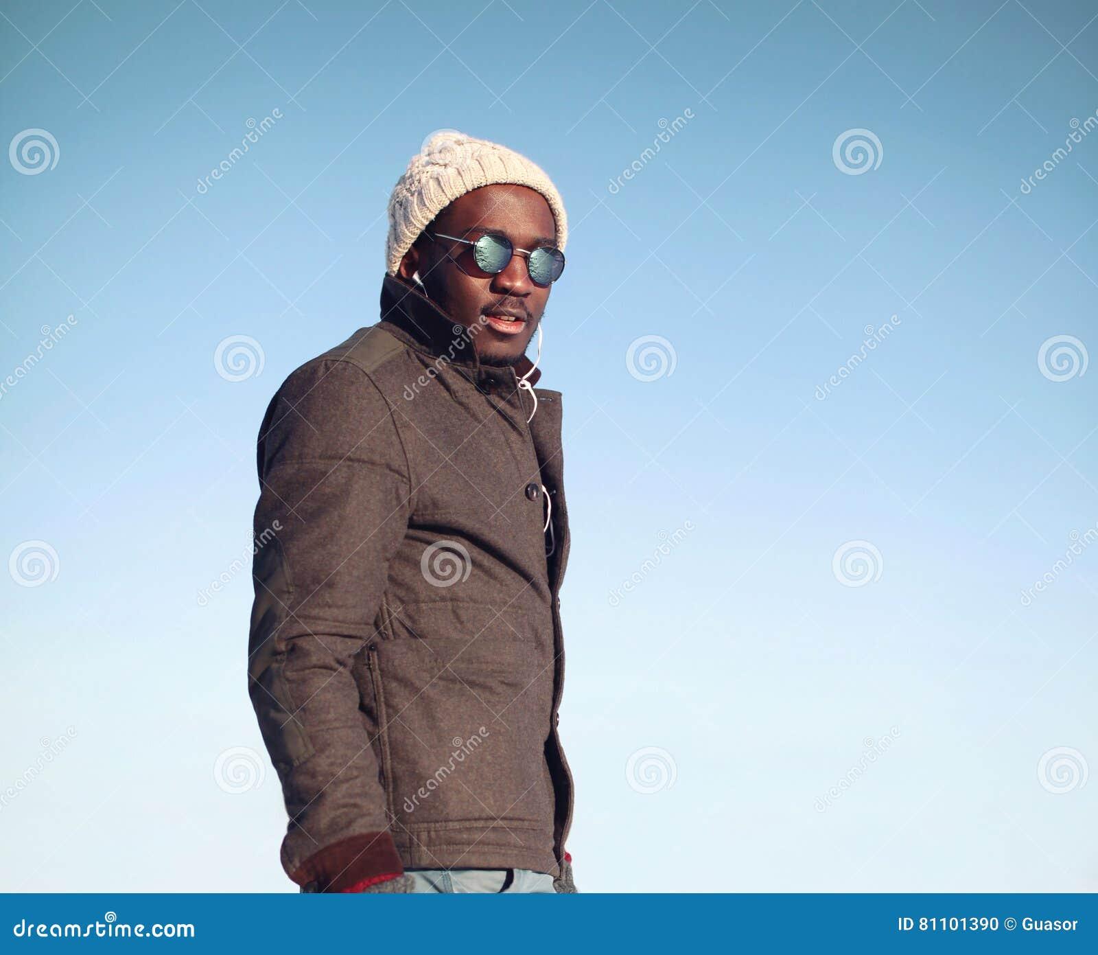 94d0740c9 El hombre africano del retrato de la moda escucha la música en invierno  sobre el cielo