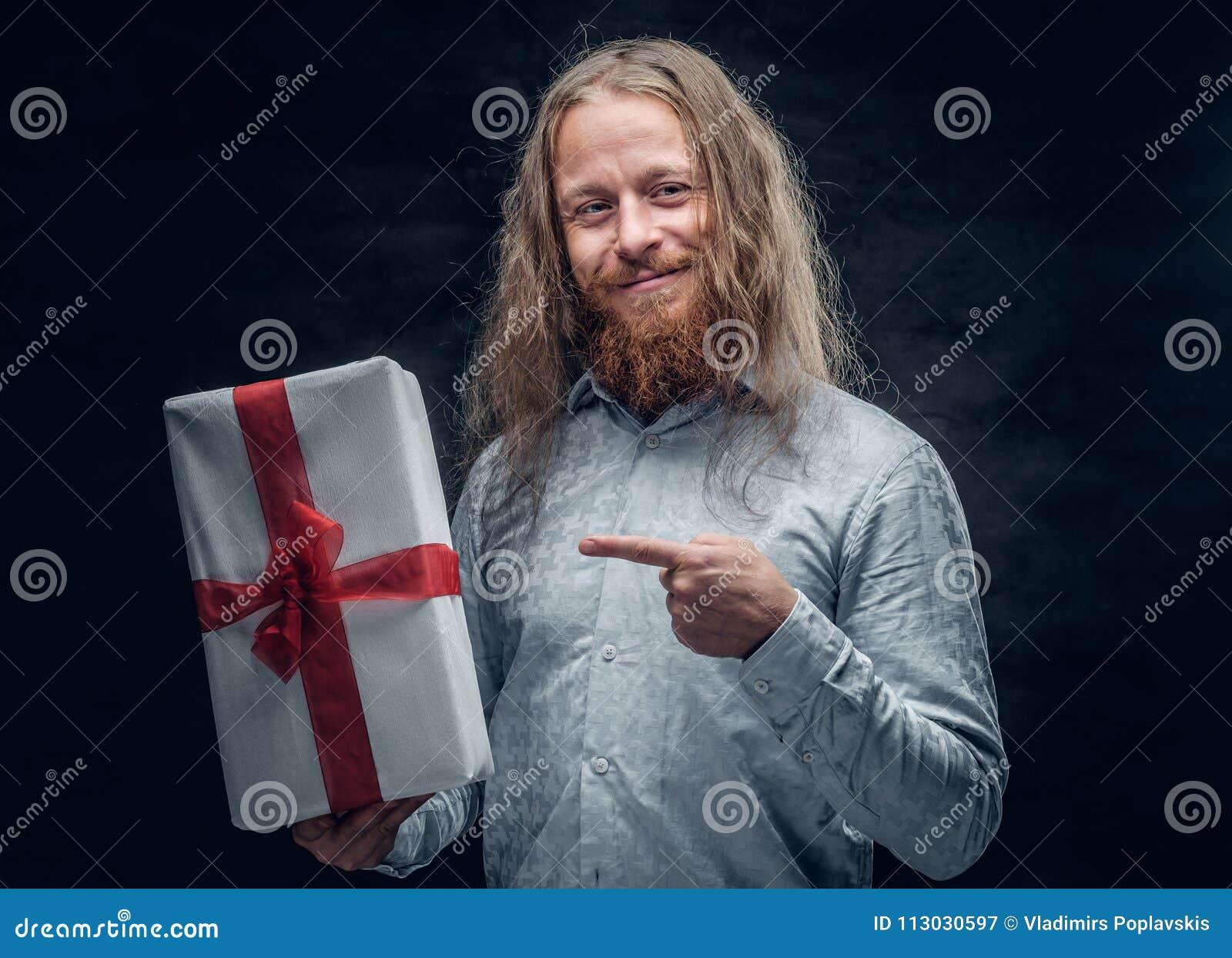 El hombre barbudo con el pelo largo sostiene la actual caja