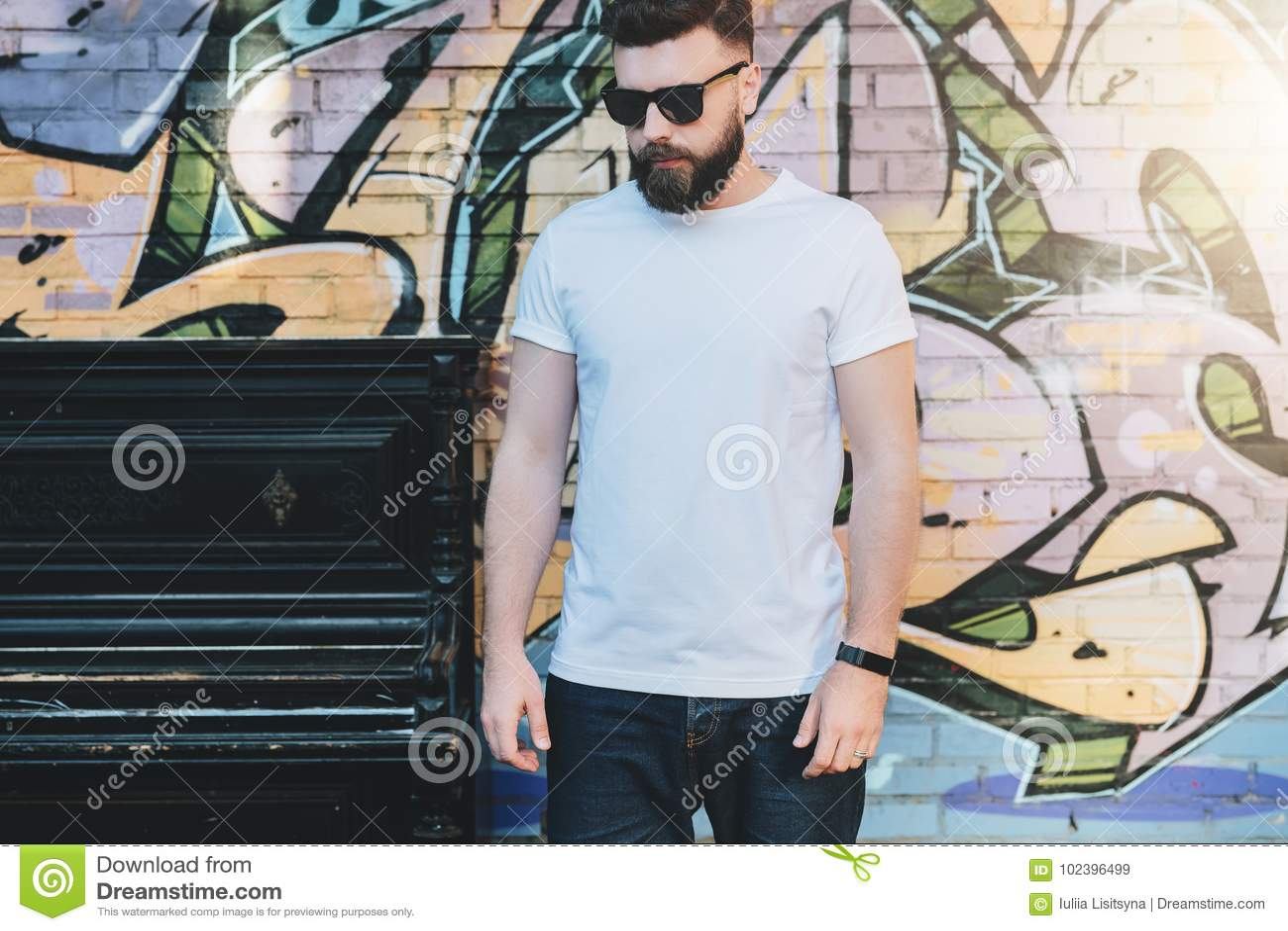 El hombre barbudo del inconformista vestido en la camiseta blanca es soportes contra la pared con la pintada Mofa para arriba Esp