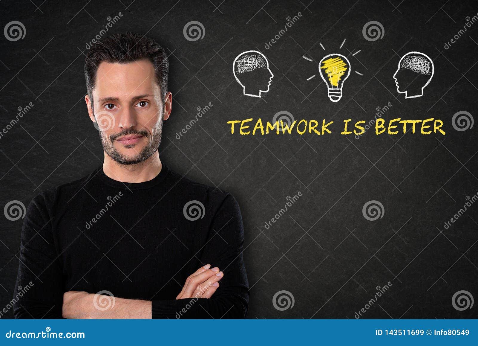 El hombre barbudo joven con los brazos cruzados, las cabezas con los cerebros, la bombilla-idea y el texto 'trabajo en equipo es