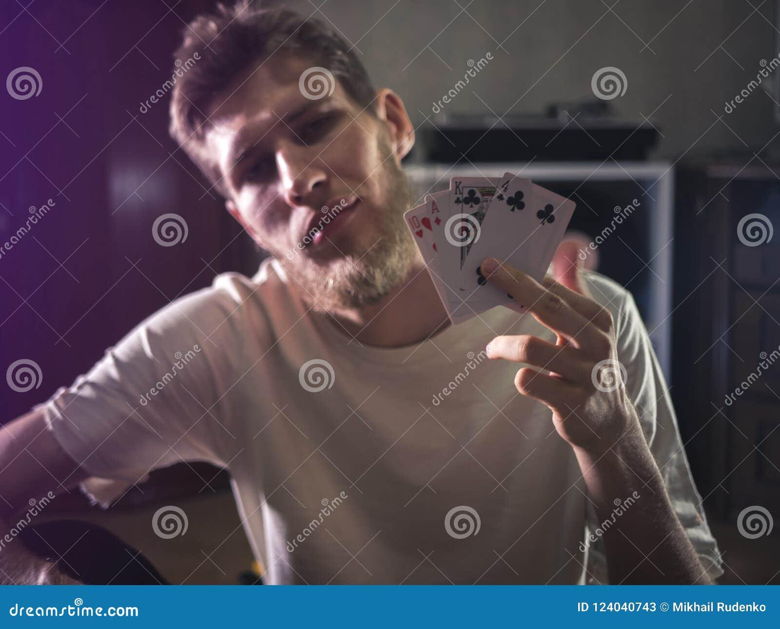 El hombre barbudo joven en tarjetas casuales del playng que se sostienen muestra el retrato de algunos trucos en casa