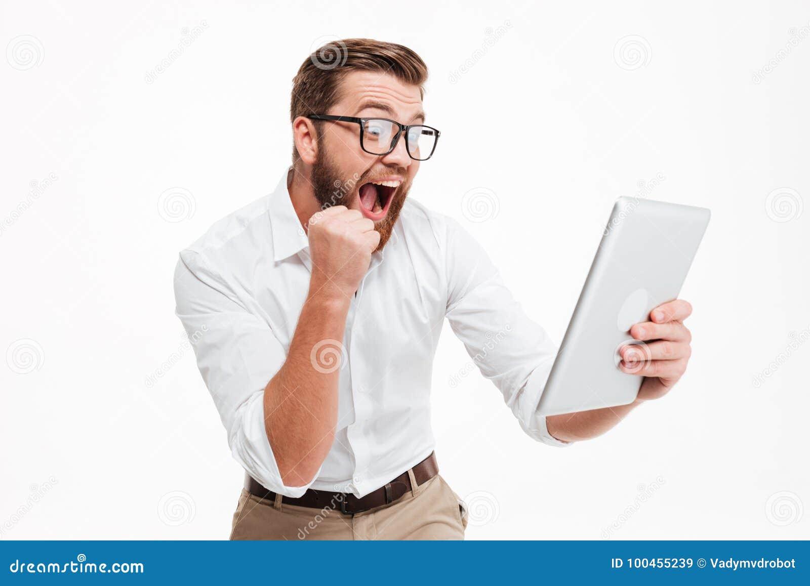 El hombre barbudo joven feliz que usa la tableta hace gesto del ganador