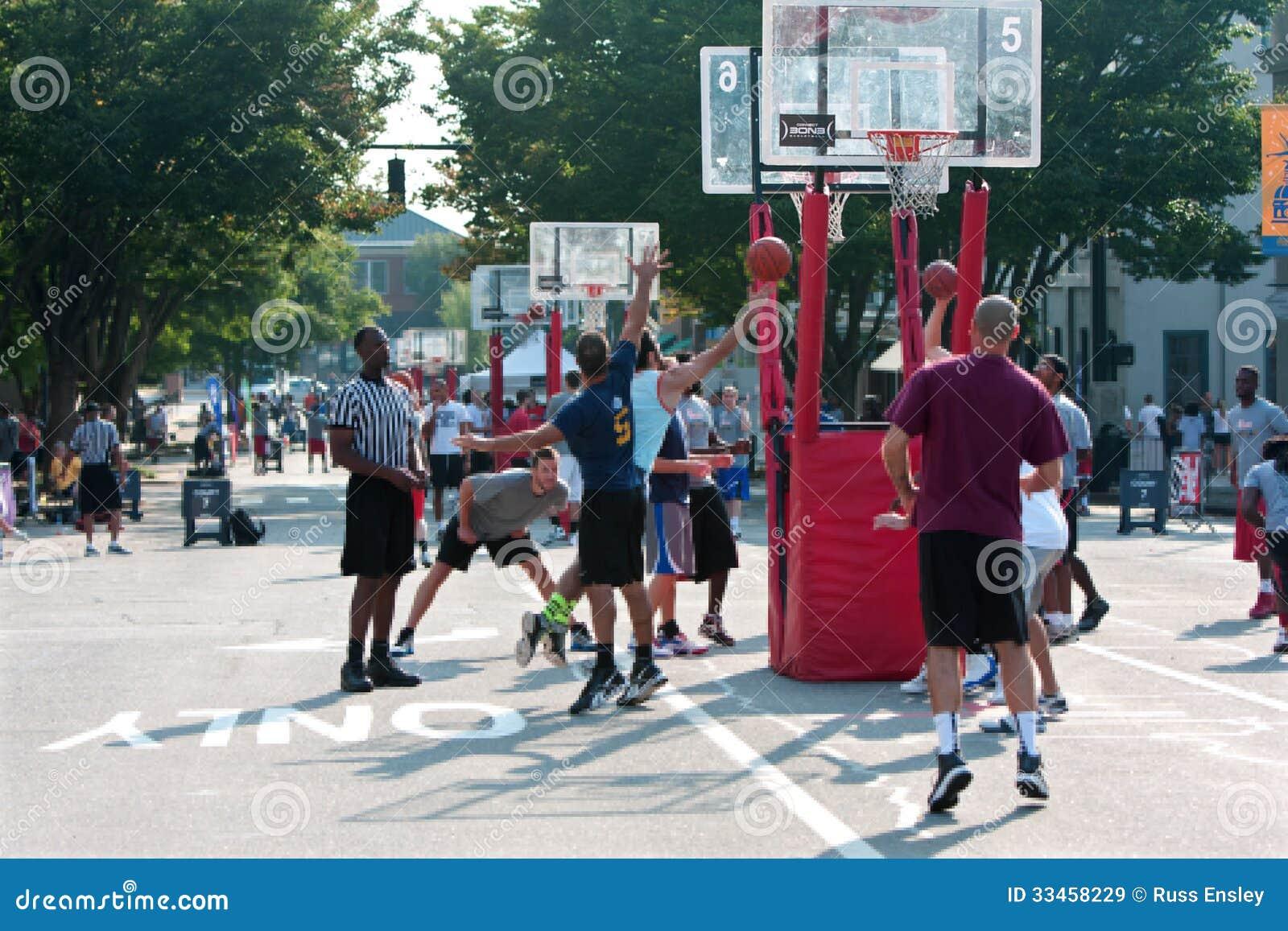 El hombre conduce y tira el Layup en el torneo del baloncesto de la calle